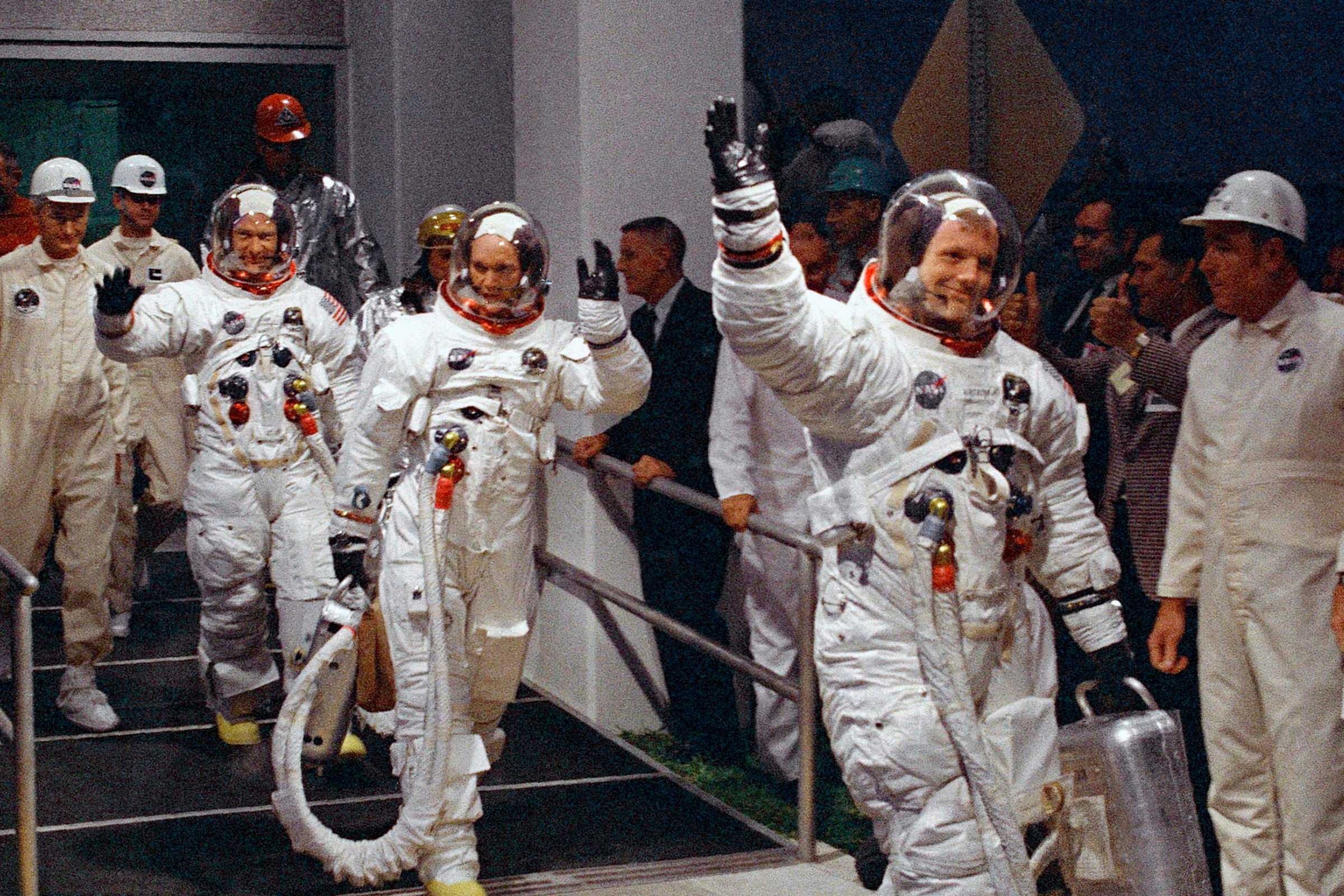 The crew, already in their flight suits, walk to the vehicle that will transport them to the Saturn V launch vehicle.