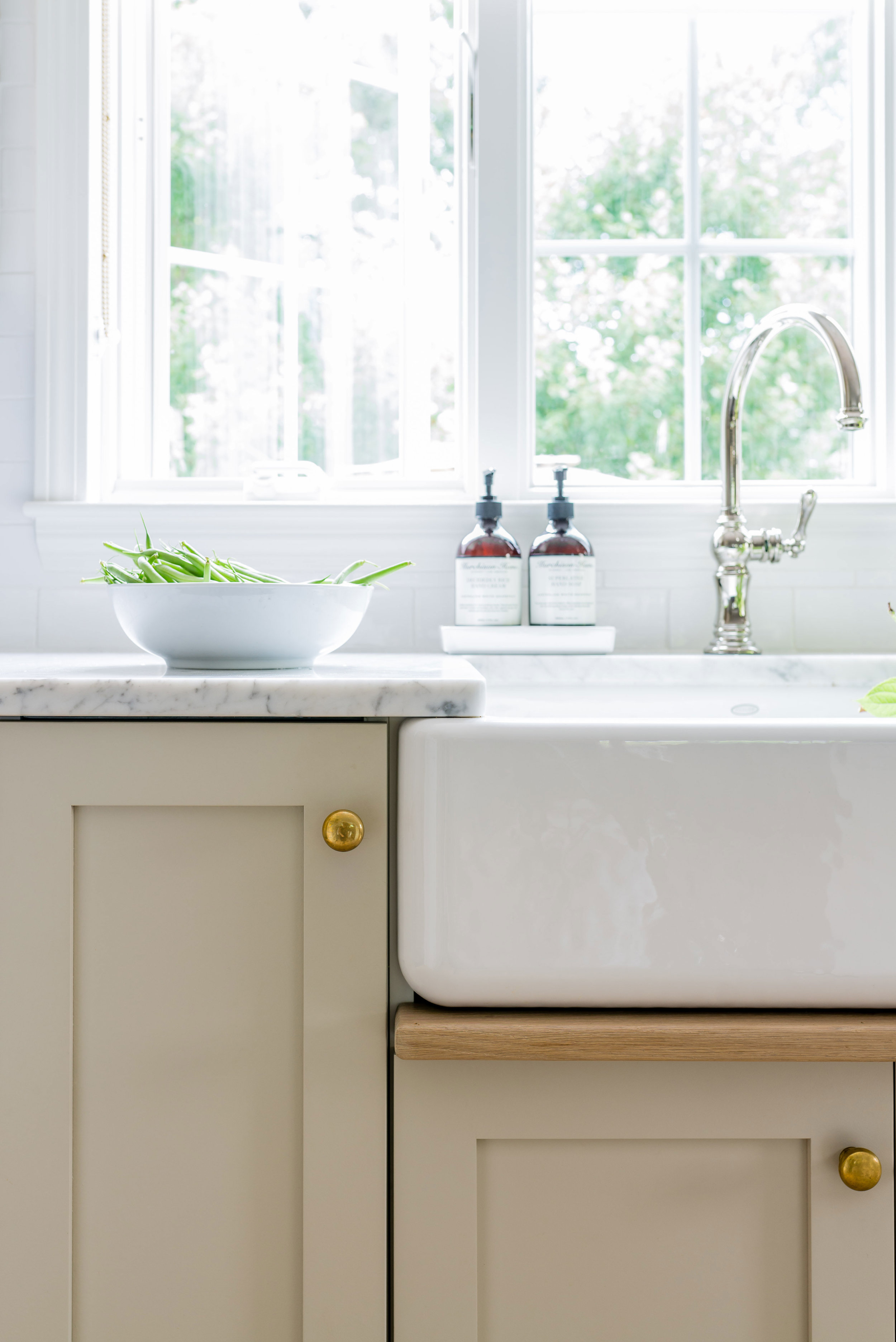 """Cabinets are customized IKEA boxes, painted with  Farrow & Ball Drop Cloth 283 . Cabinet hardware is unlaquered brass pulls and knobs from  House of Antique Hardware . Countertops are honed Carrera marble from  Gerrity Stone . The sink is Whitehaven 30"""" from Kohler. Faucet is  Kohler Artifacts . Design:  Christina Wikman Interiors  // Photo:  Jessica Delaney"""