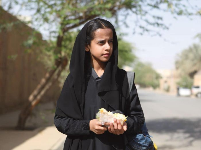 Image description: A girl around 11 years old (Wadjda) stands in the middle of the street holding food in her hands. She is wearing a headscarf.