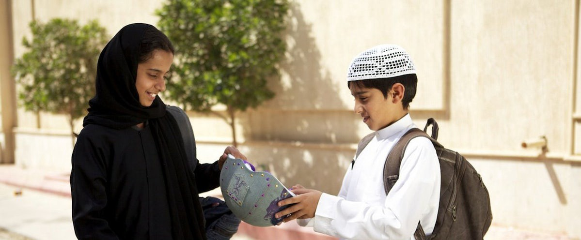 Image description:  Wadjda is on the left of the frame in a black headscarf and a black dress holding a backpack. She is being handed a bicycle helmet by the boy on the right in a white shirt, white hat, and holding a brown backpack.