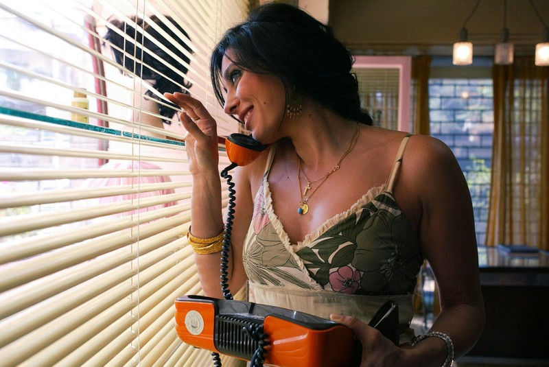 Image description: Layle from the movie  Caramel  holding an old fashioned, orange, corded phone in one hand and looking out window slats with her other hand. She is smiling into the phone.