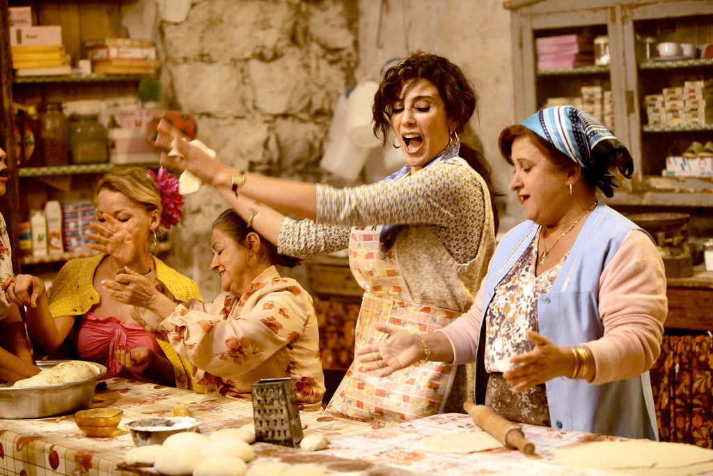 Image description: The women in the movie  Where Do We Go Now?  baking together in a home. There are four women in the frame making big movements, singing, and laughing.