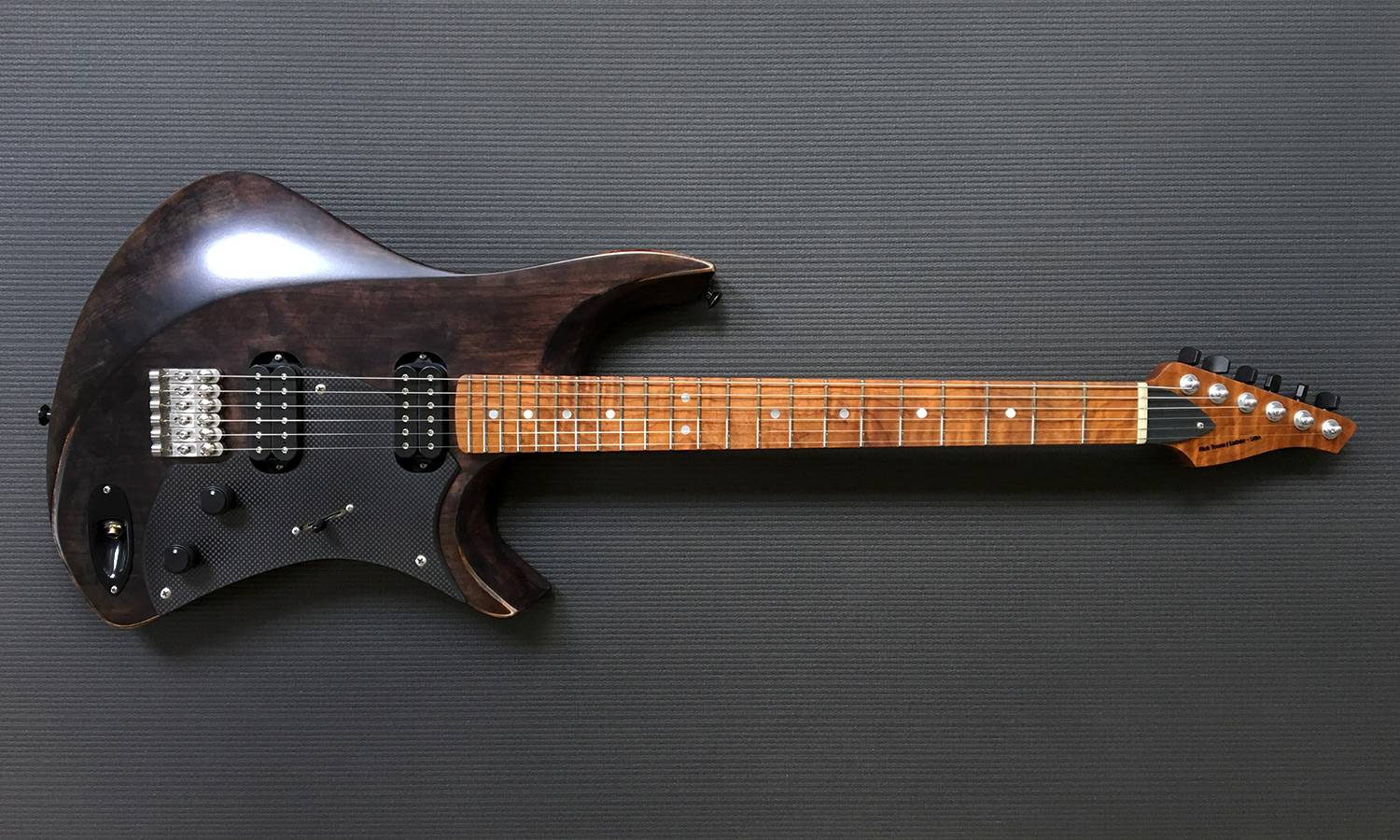 PHOTO: Intonation Cantilever™ precision machined stainless steel solo bridges, Carbon fiber pickguard, OEM DiMarzio pickups. Note jack location on this custom guitar.