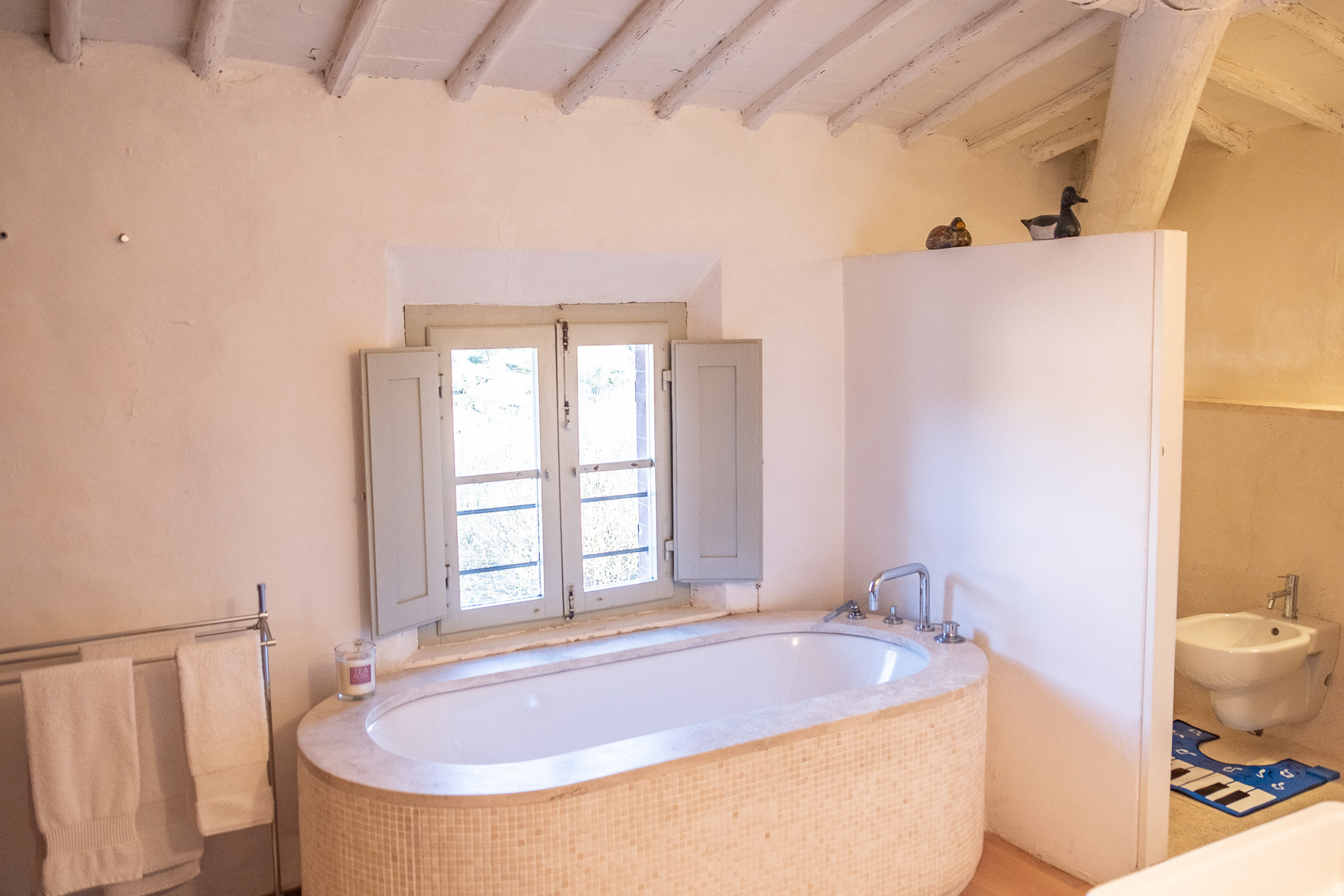 The girls bathroom with  our bath. Quite often I have a bath at night with the candles and I can see the Duomo and the Center of Siena from the window. Just magic.