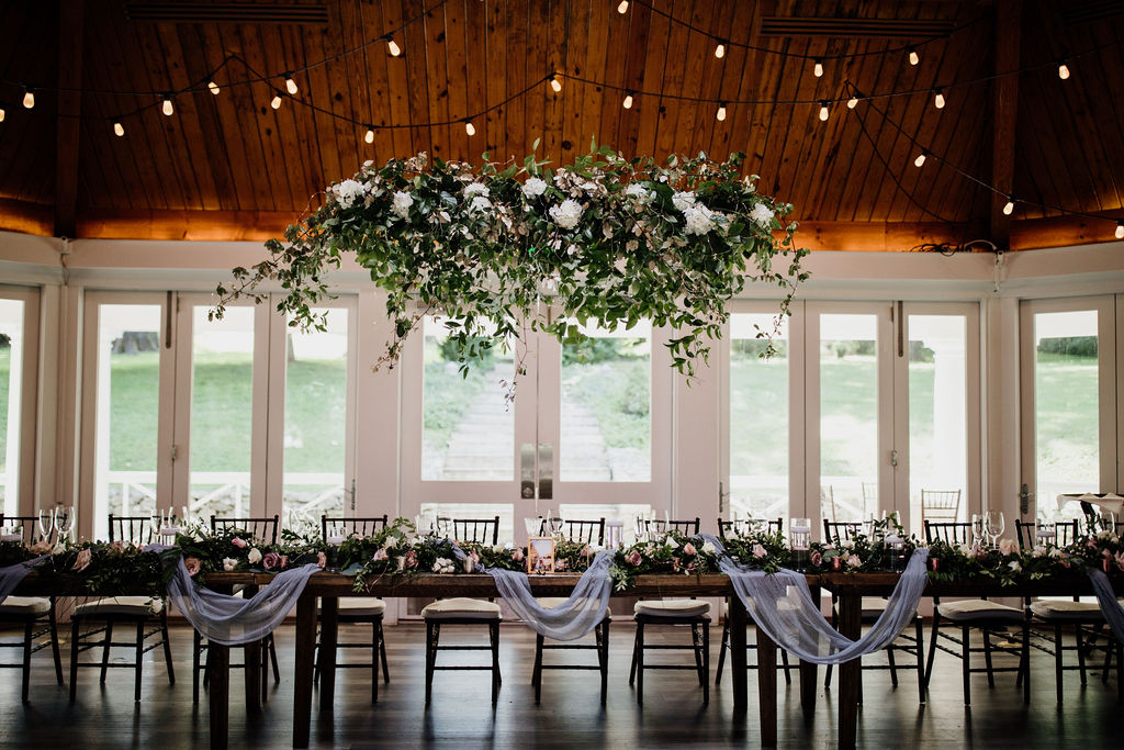 We love a challenge… - When collaborating with the bride and her mother, one of the things they really wanted was a way to hide an exit sign right above their kings table. We created this beautiful hanging installment for Emily & Jeff's gorgeous reception! The floating greenery included pops of white blooms and warm fairy lights to create a truly romantic setting.