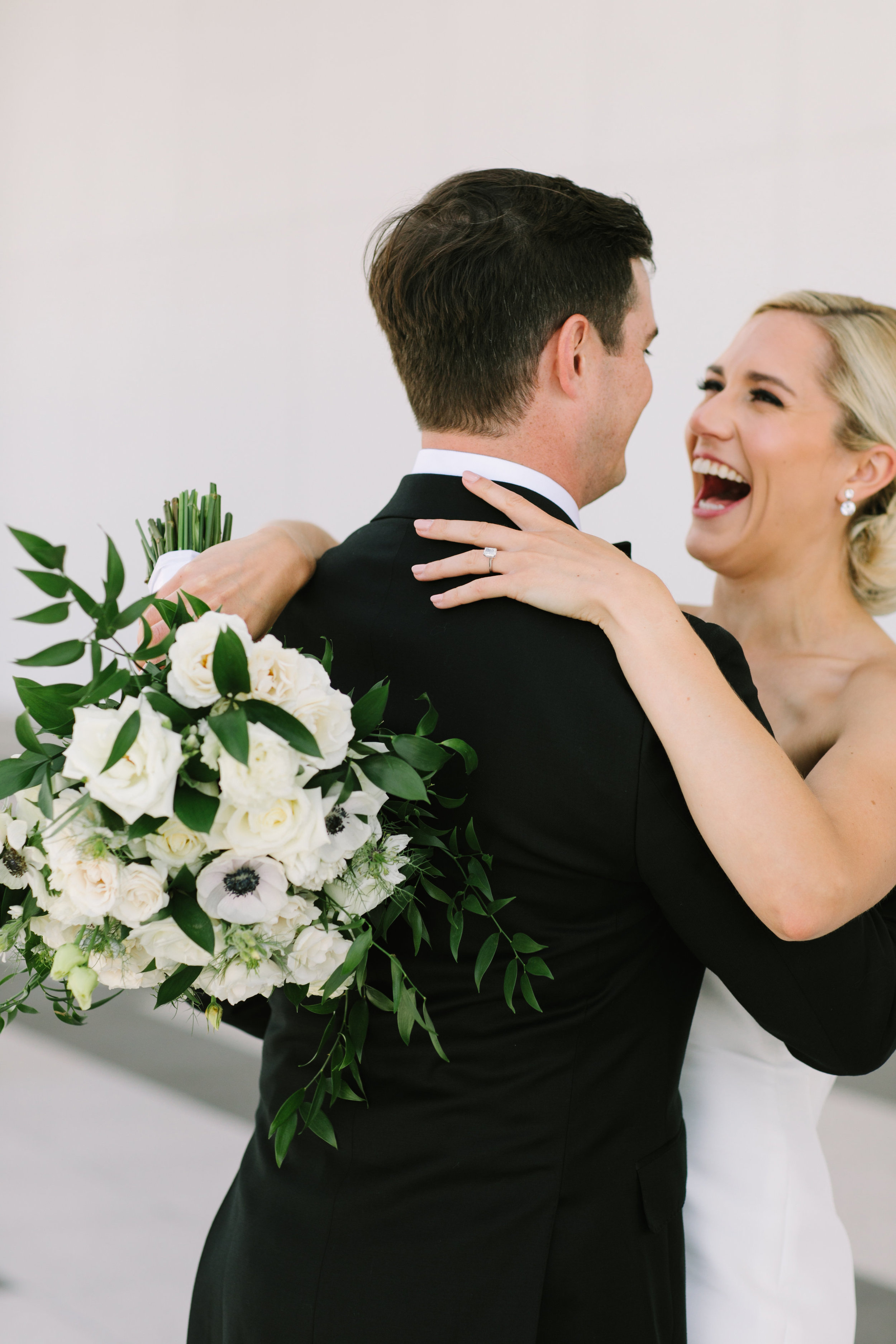 Perfect First Look - Their first look couldn't have been more perfect. These pictures give us all the feels!! We love the backdrop of the Kennedy Center for these photos. The blacks, whites and greenery mix with the clean lines of the background to create a look at is beautifully classic and fresh!