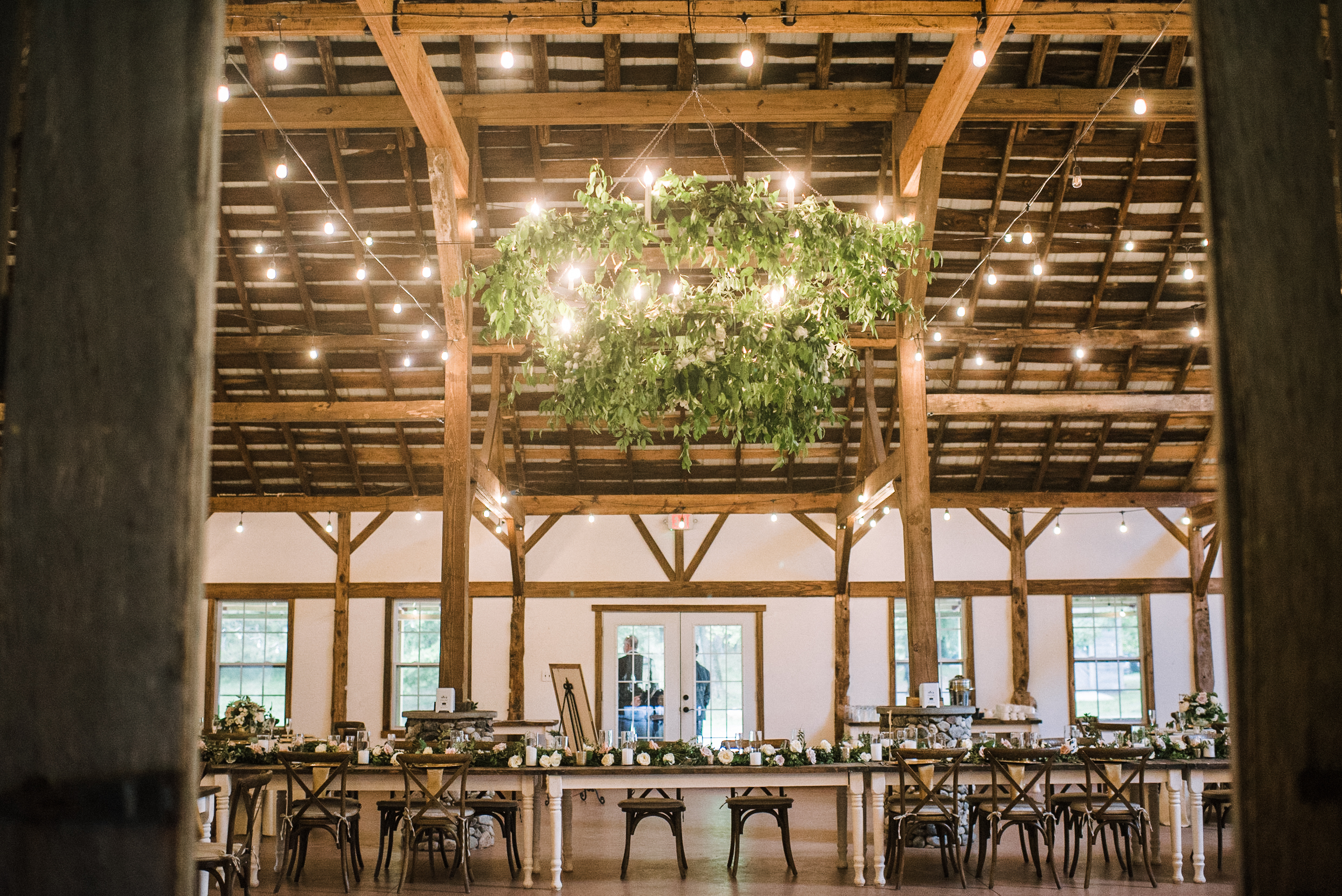 Reception in the stable… - Sarah & Andrew's vision for their reception was such a joy for us to help bring to life! We loved creating this chandelier with draping greenery above the kings table.