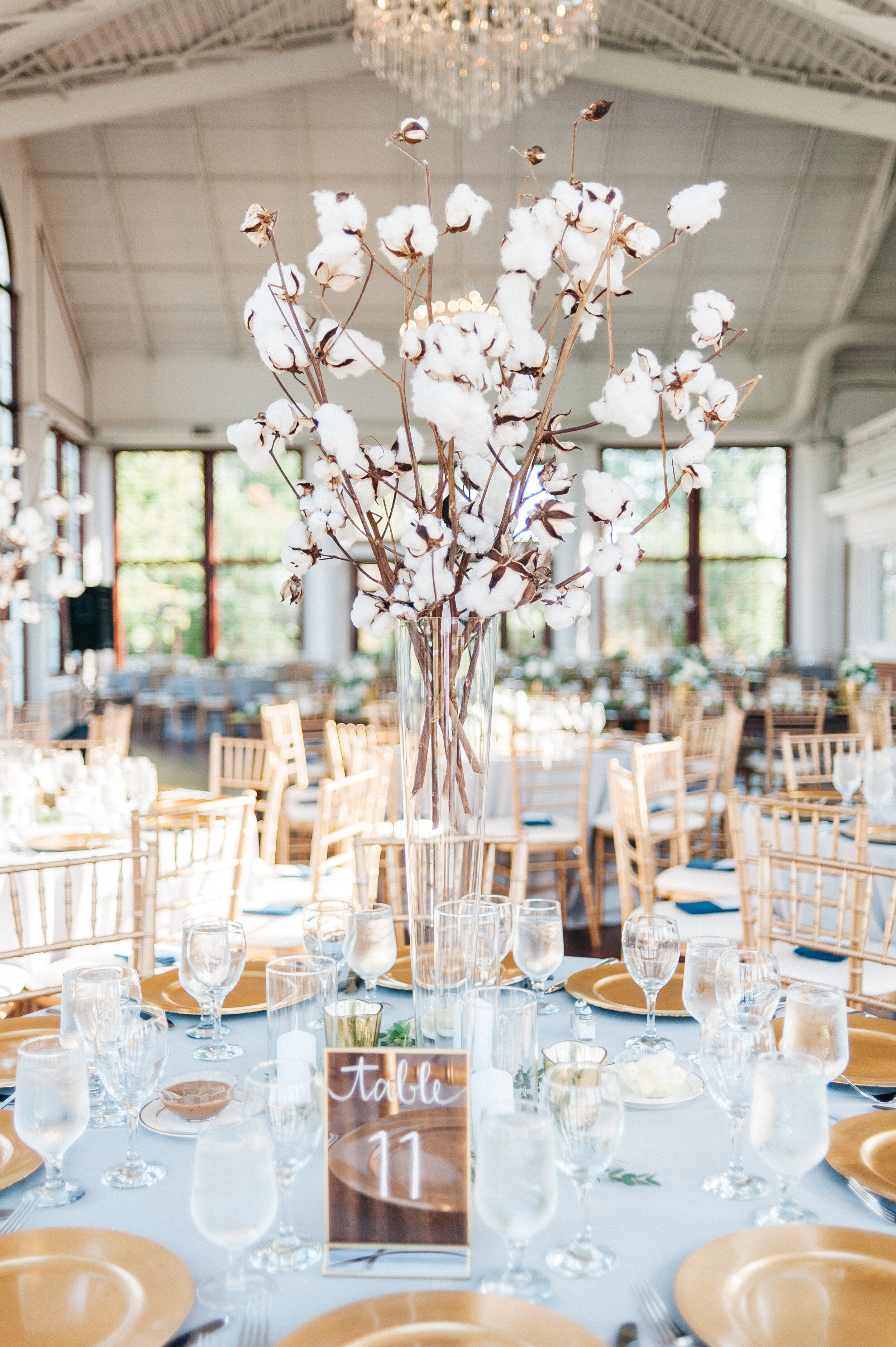 Reception - These tall cotton arrangements were so unique and perfect for the reception! We also repurposed the arrangements from the rehearsal dinner the night before. We love how all the blues, golds and whites came together. And how fun are the smores trailmix favors?
