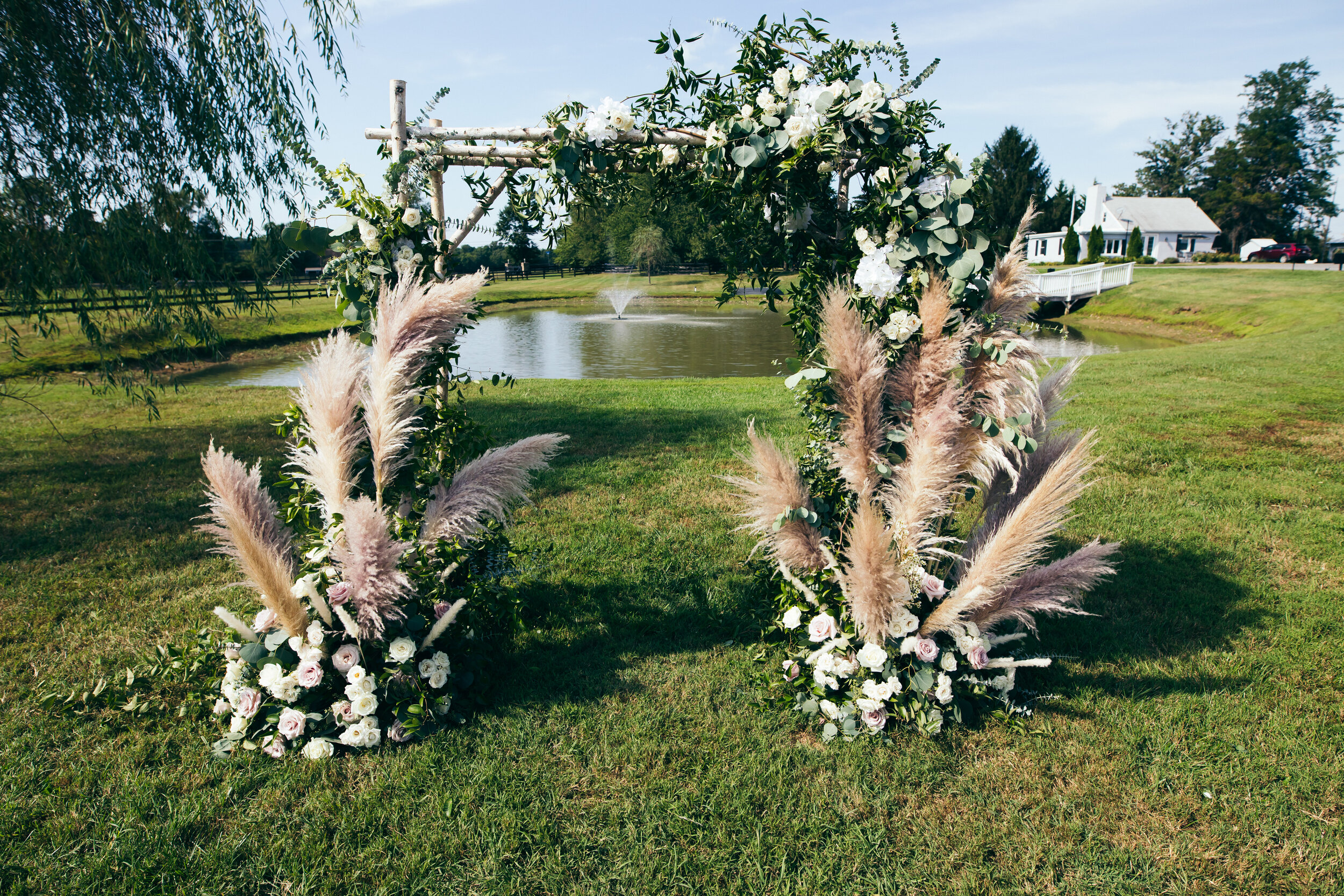 This Arch! - For this arch, we used lots of pampas grass mixed with greenery & florals for a really whimsical & boho aesthetic. The pond &beautiful grounds in the background made the perfect backdrop for this truly special ceremony.