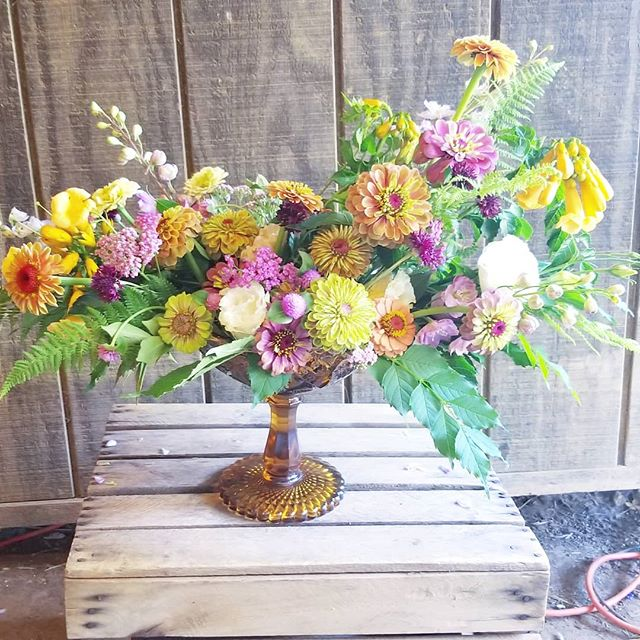 A little fun on the farm! Chelsea at @beeswingfarm wanted to see this amber compote in action, so I happily assisted. It was a good creative workout to try new styles and use bright colors to capture the beauty of the farm during July. Stay cool, y'all!  #farmtotable #colorfulwedding #risingtidesociety #centerpieces #zinnias #summerflowers #summersolstice #underthefloralspell #wvflorist