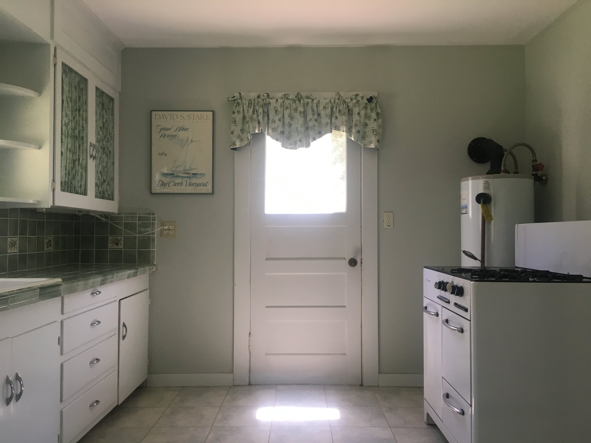 Kitchen with stove, water heater, cabinets and back door on the Yorkville listing In Mendocino County.
