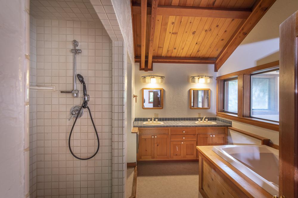 Large bathroom, tiled shower, tub, wood finishes.