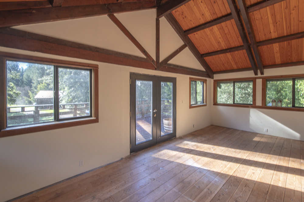 Open living space with beautiful wood beams, floors and windows.