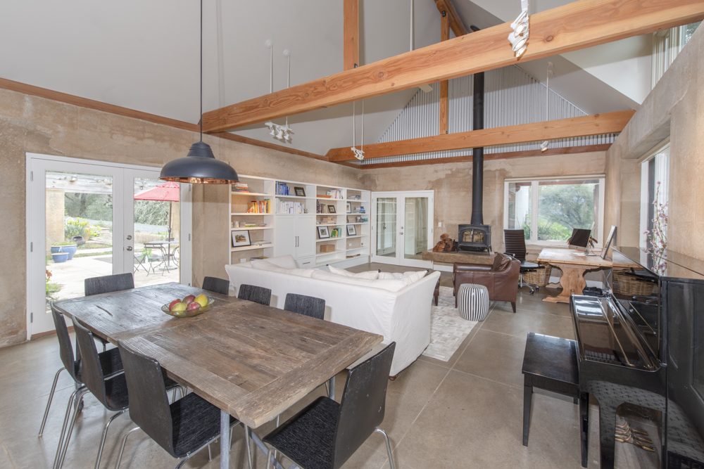 over head beams, wood stove, dining room double doors to patio.