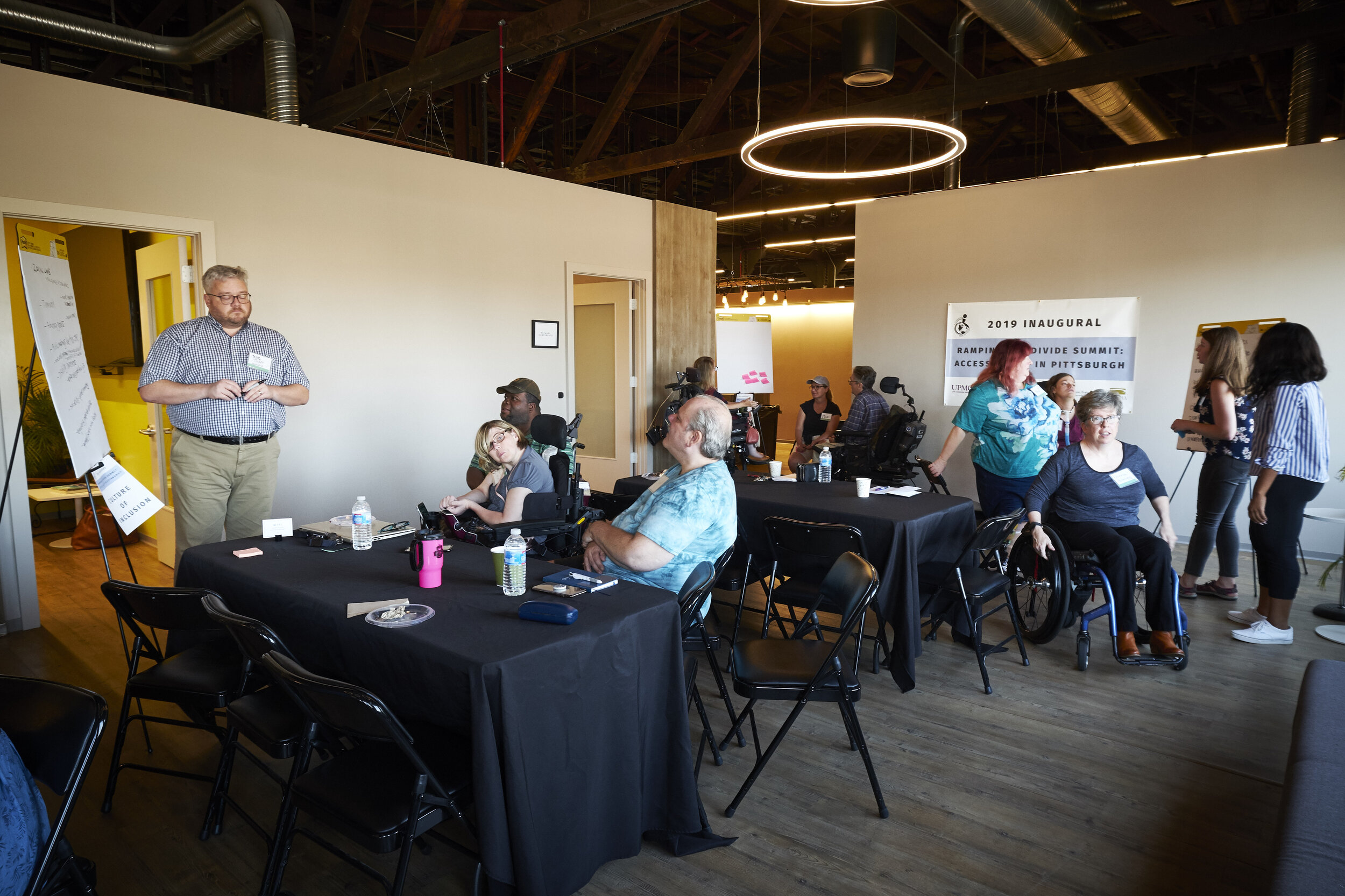 A group of participants are pictured talking. They are divided into small groups. Some are writing ideas on tablets, and others are gathered around listening.