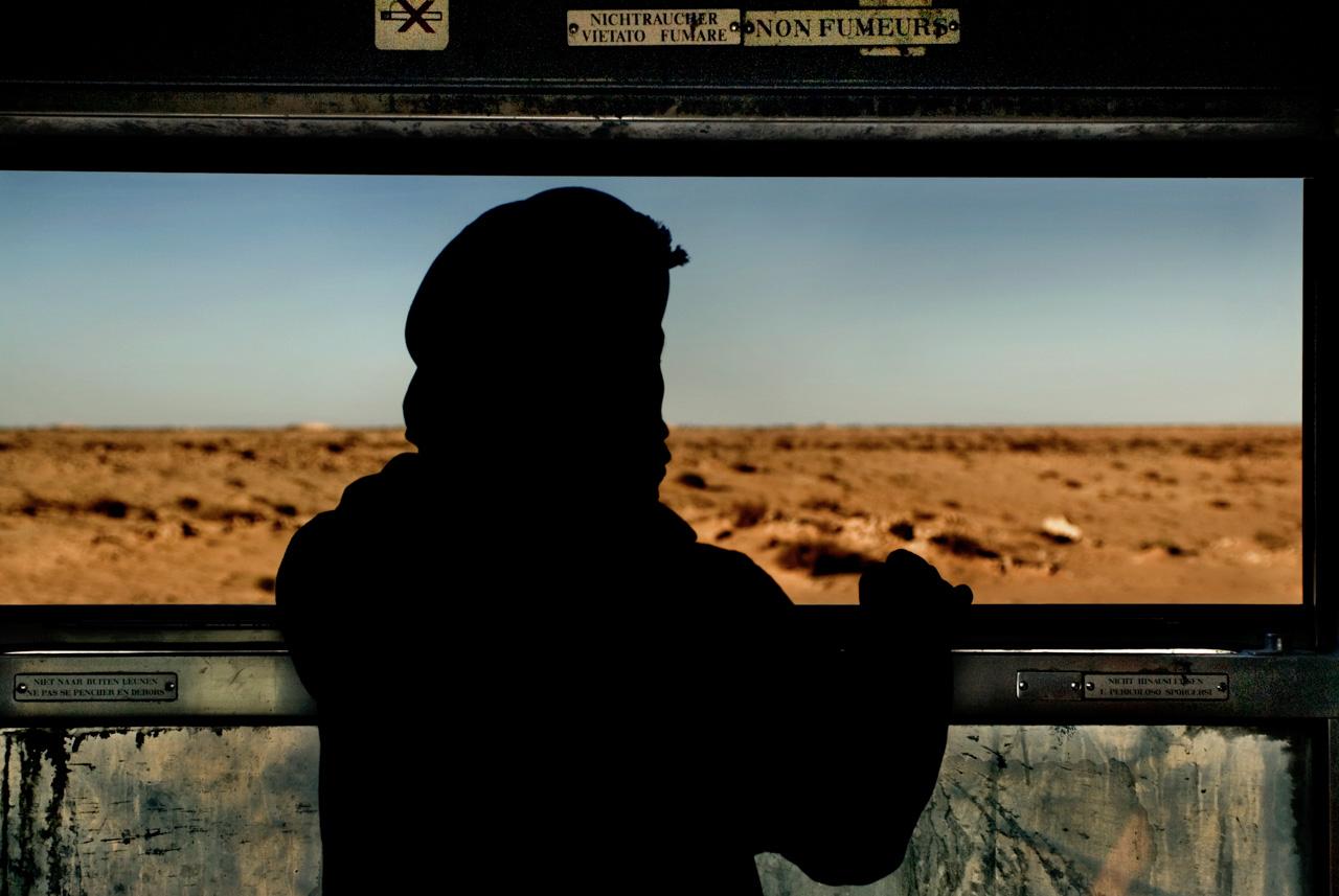Ogni giorno il treno attraversa il deserto della Mauritania per collegare Zouerat - città mineraria del Sahara settentrionale scoperta negli anni venti dai francesi - a Nouadibou, crocevia di pescherecci, di merci e di migranti affacciato sull'Atlantico. Diciotto ore il viaggio sui seicentocinquanta chilometri di binari che attraversano la distesa di sabbia.Ogni tipo di mercanzia aspetta di trovare il suo posto sui vagoni e quando il treno arriva c'è già chi lancia, chi afferra e chi carica. Sacchi che salgono, mani che scendono: lo sforzo collettivo di una folla indisciplinata in cui tutti prendono posto, montoni e capre compresi.