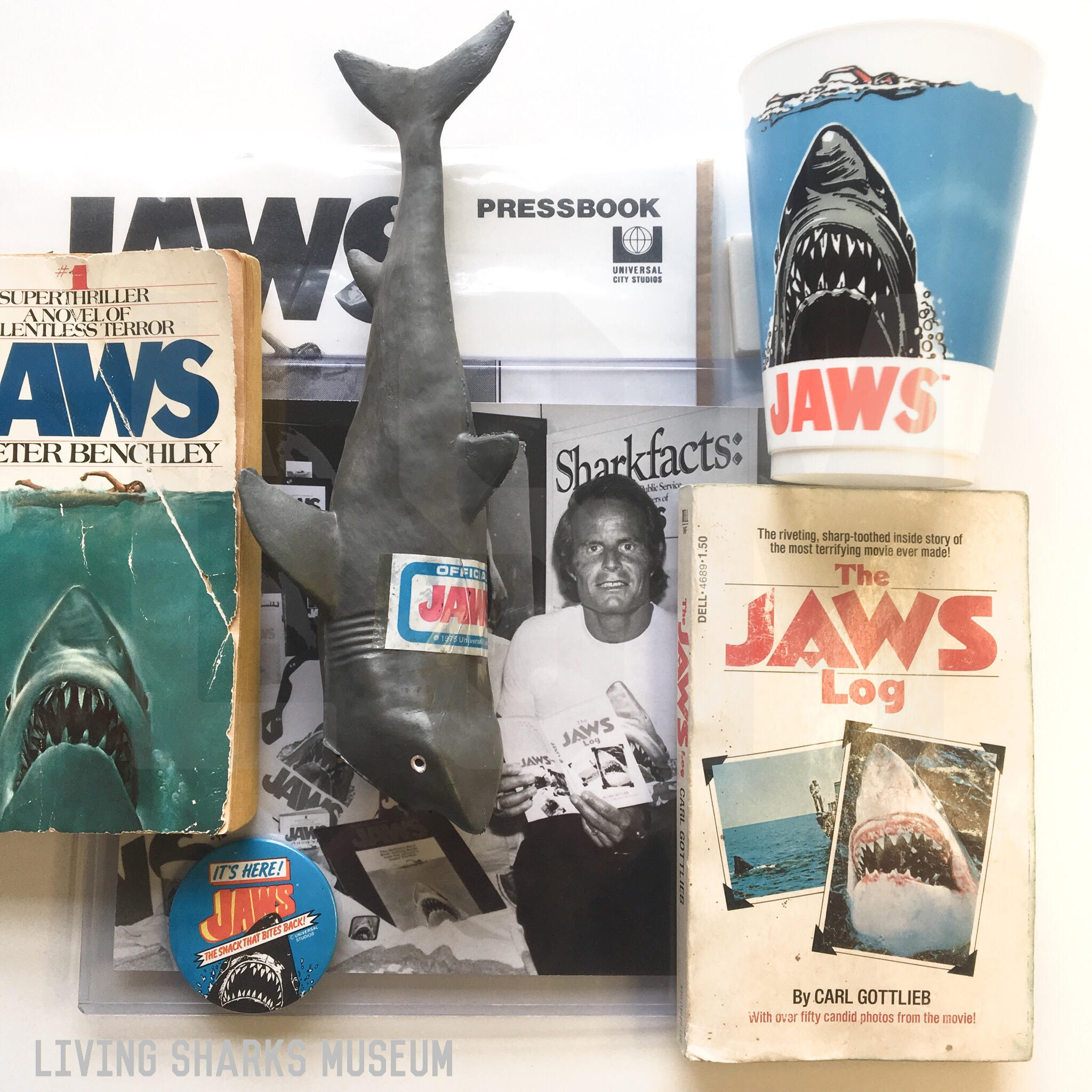 """JAWS '75 MERCH - When Universal realized the potential after the opening of Jaws in 1975, the producers greenlit countless merchandising deals. Collectibles ranged from posters, books, jewelry, clothing, rubber sharks, drink cups, etc. This included the book The Jaws Log, a post-release rush-written """"diary"""" of the making of the film, commissioned to Jaws screenwriter Carl Gottlieb, who also portrayed the newspaper reporter in the film.The press photograph shows Jaws producer Richard Zanuck amongst the whole array of advertising and merchandising materials made to satisfy public craving._____________________JAWS RUBBER SHARK TOY 1975JAWS DRINK CUP 1975JAWS LOG by CARL GOTTLIEB 1975Private Collection - Keith M. Cowley"""