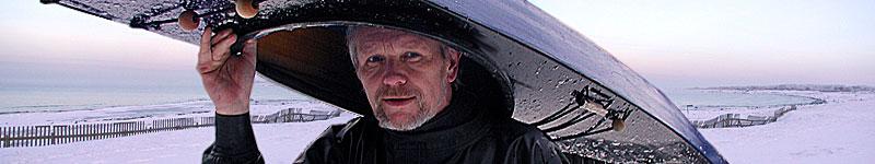 Björn Thomasson en tidig vintermorgon med Black Pearl i Haverdal.  Grönlandskajaker bärs enklast med aktern före, huvudet på sitsen och axlarna på sargkanten. Foto: Ninna Thomasson