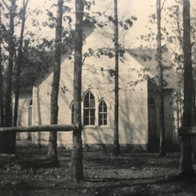 The old Round Grove Baptist Church building with hitching posts outside