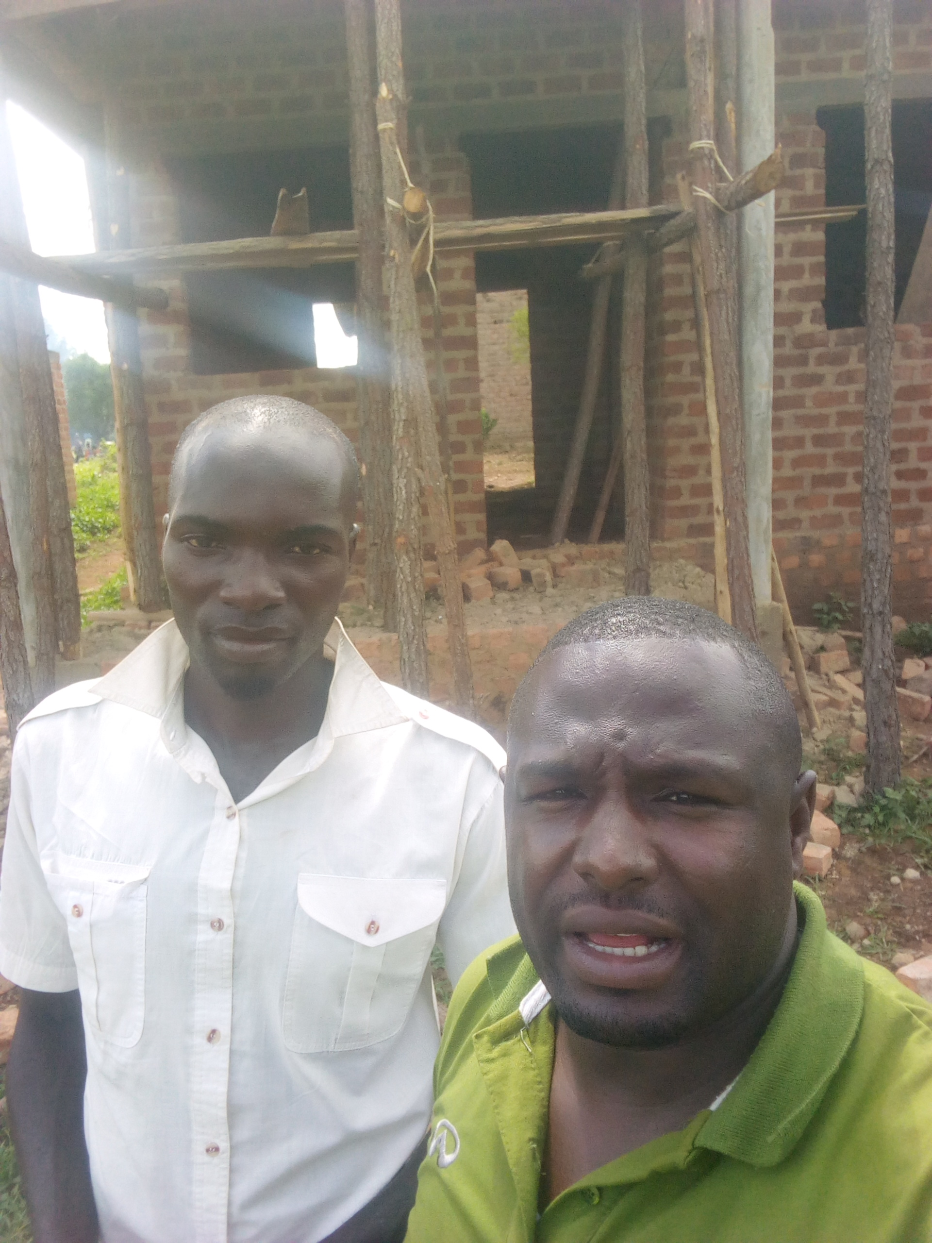 Kanna (left) in front of his home-in-progess with Joseph Kalyango  inUganda