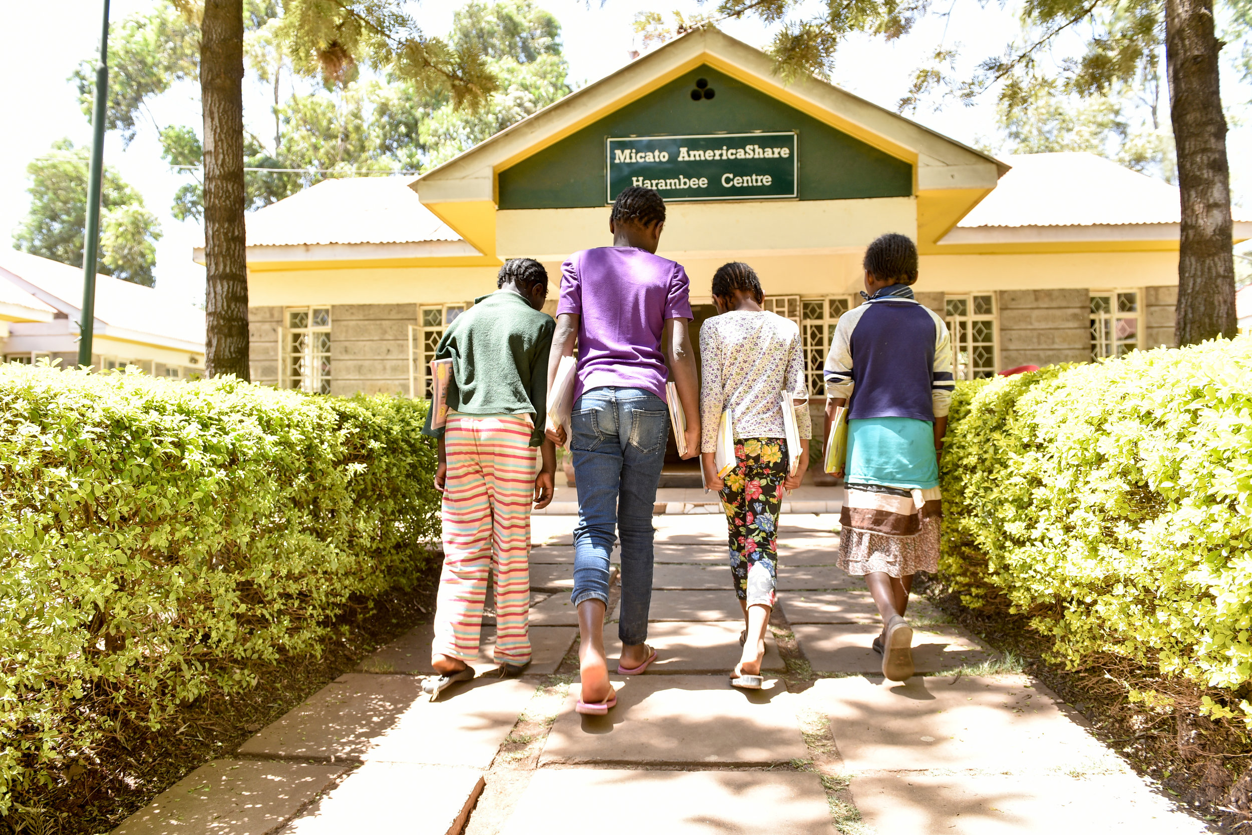 Our work - a group of children walking to the harambee center.jpg