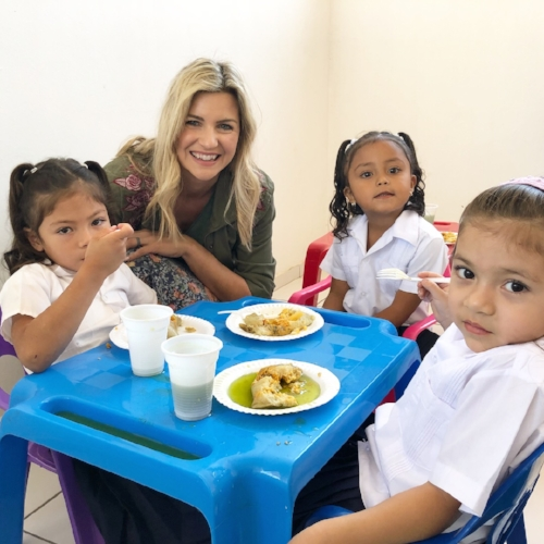 Melanie helping hand out nutritious meals to students in Honduras.