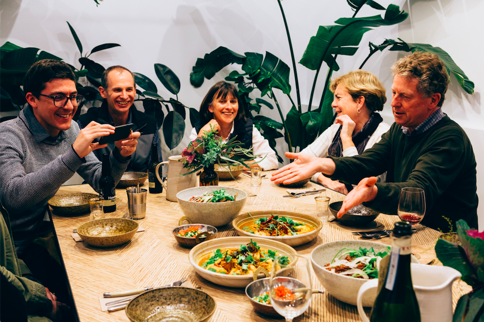 People having conversation over a beautiful meal at our Free to Feed X The Wandering Chef Dinner