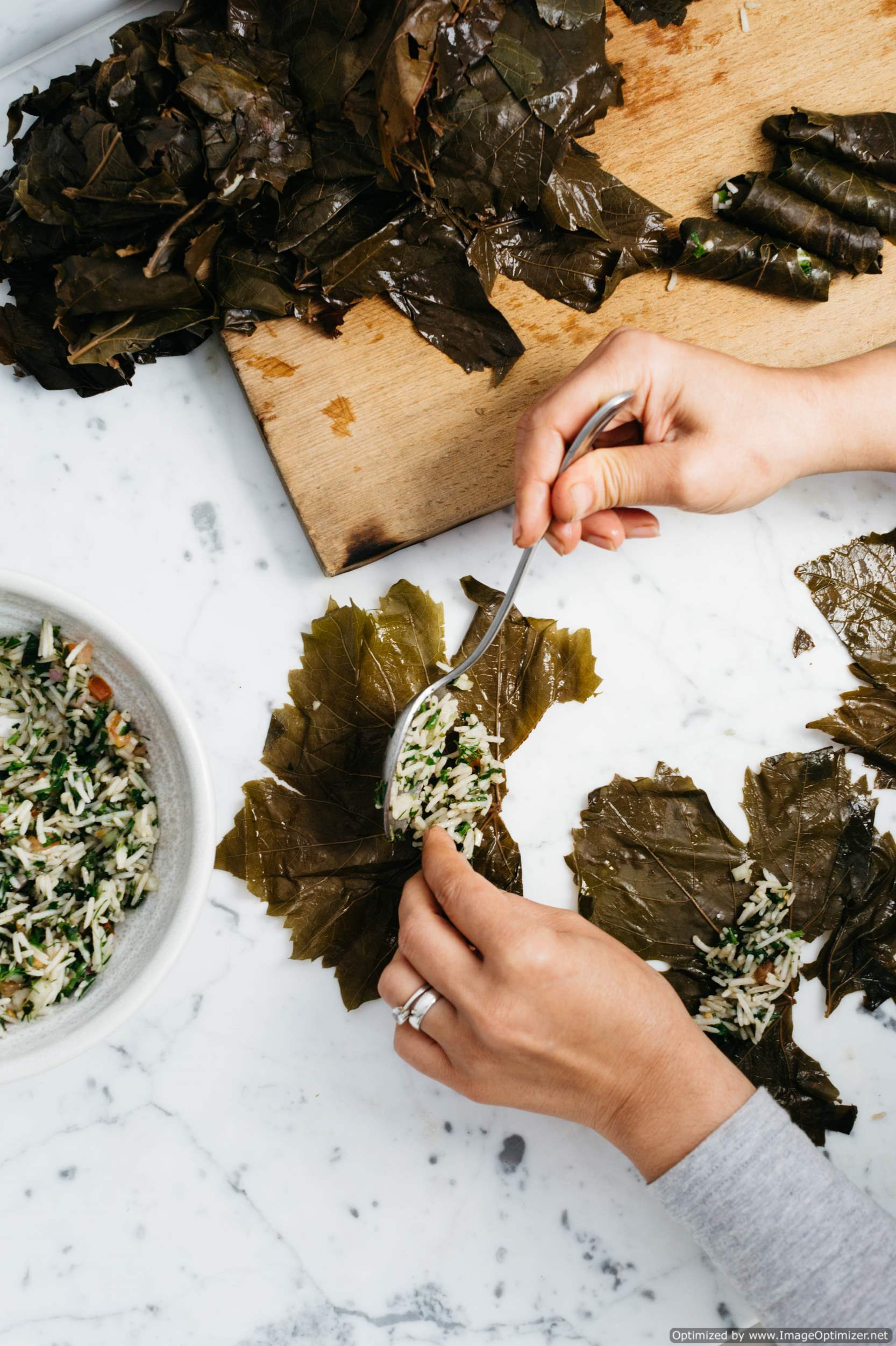 Hands preparing dolmas in green leaves.