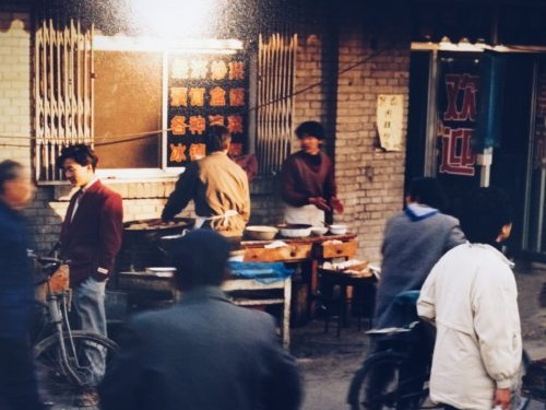 Little Fish - Nassau Weekly | October 2, 2016We were back mostly because of Yeye—because Yeye was forgetting things and faces. Every morning our two uncles took the old man on a walk by the artificial river which runs across the entrance of my grandparents' hutong.Photo: Thomas Struth, Market with Stupa, 1996.