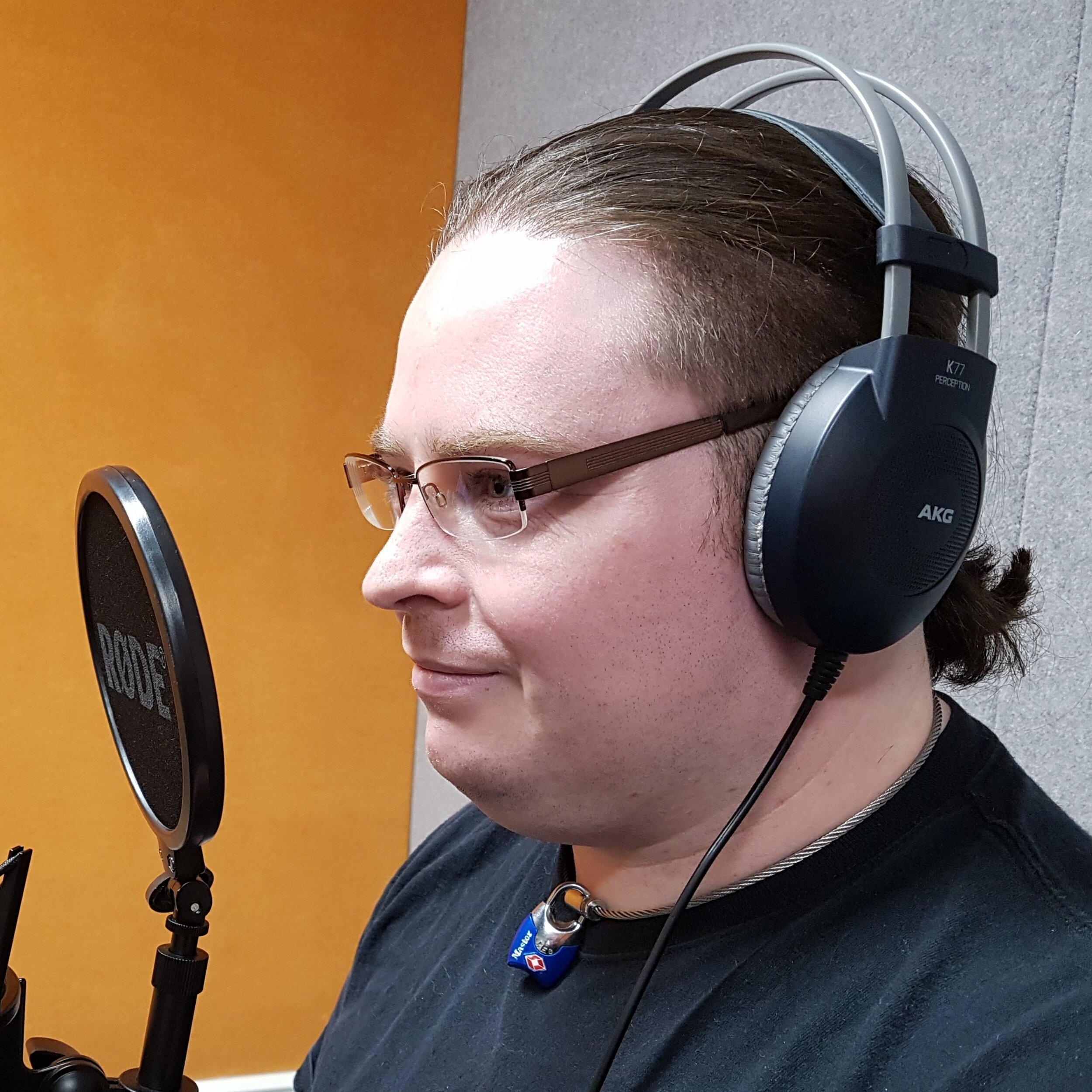Lee Davis-Thalbourne, a white man with brown hair and glasses wearing headphones, in front of a microphone.