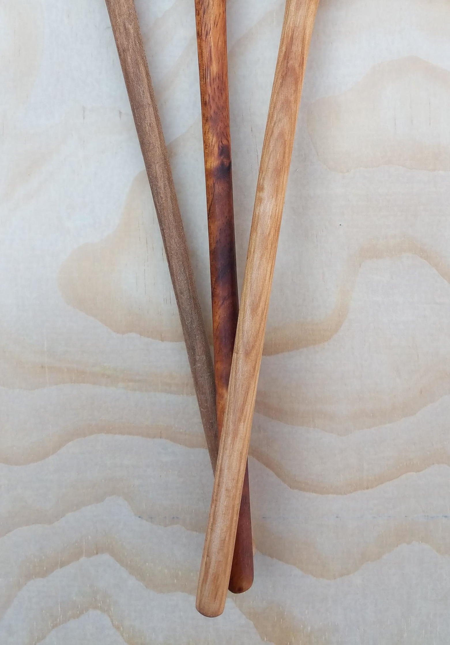 The straight, slender handles of the apothecary spoons.