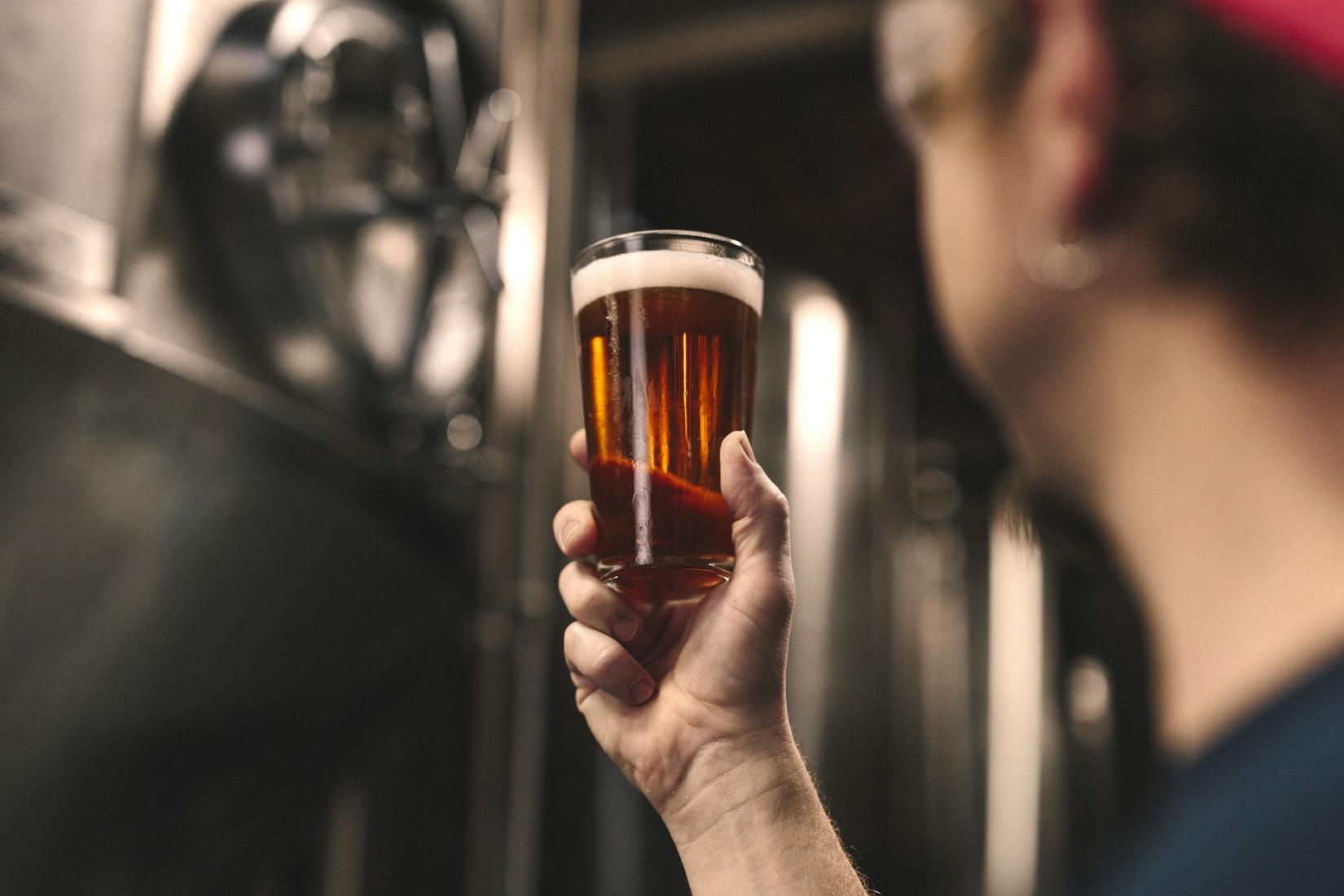 man looking at beer in glass - unsplash.jpg