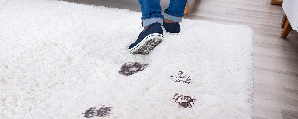 Dirty footprints on white rug