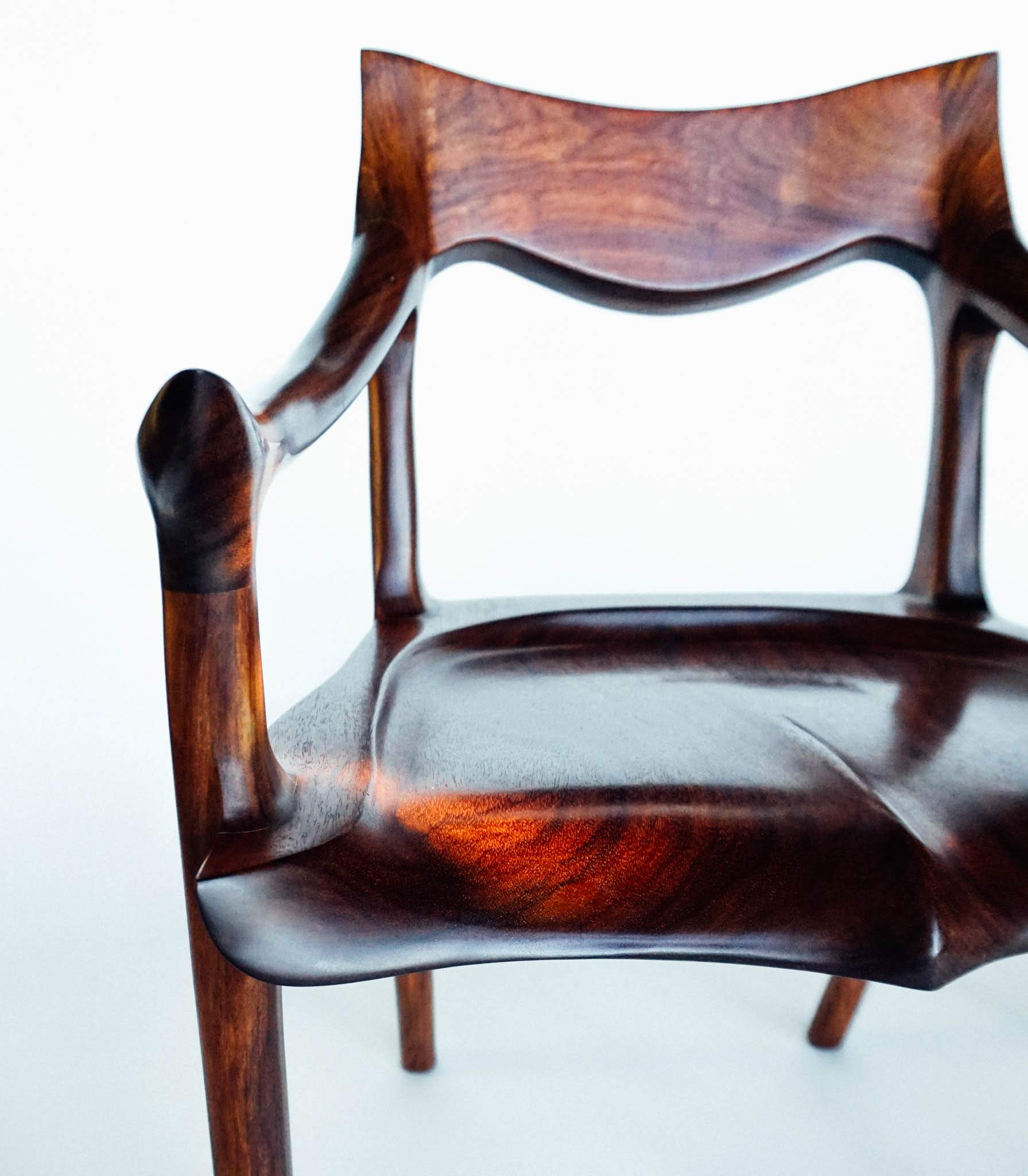 The signature down and outward curve of the arm of this chair makes it unique. It can only be achieved by hand carving.