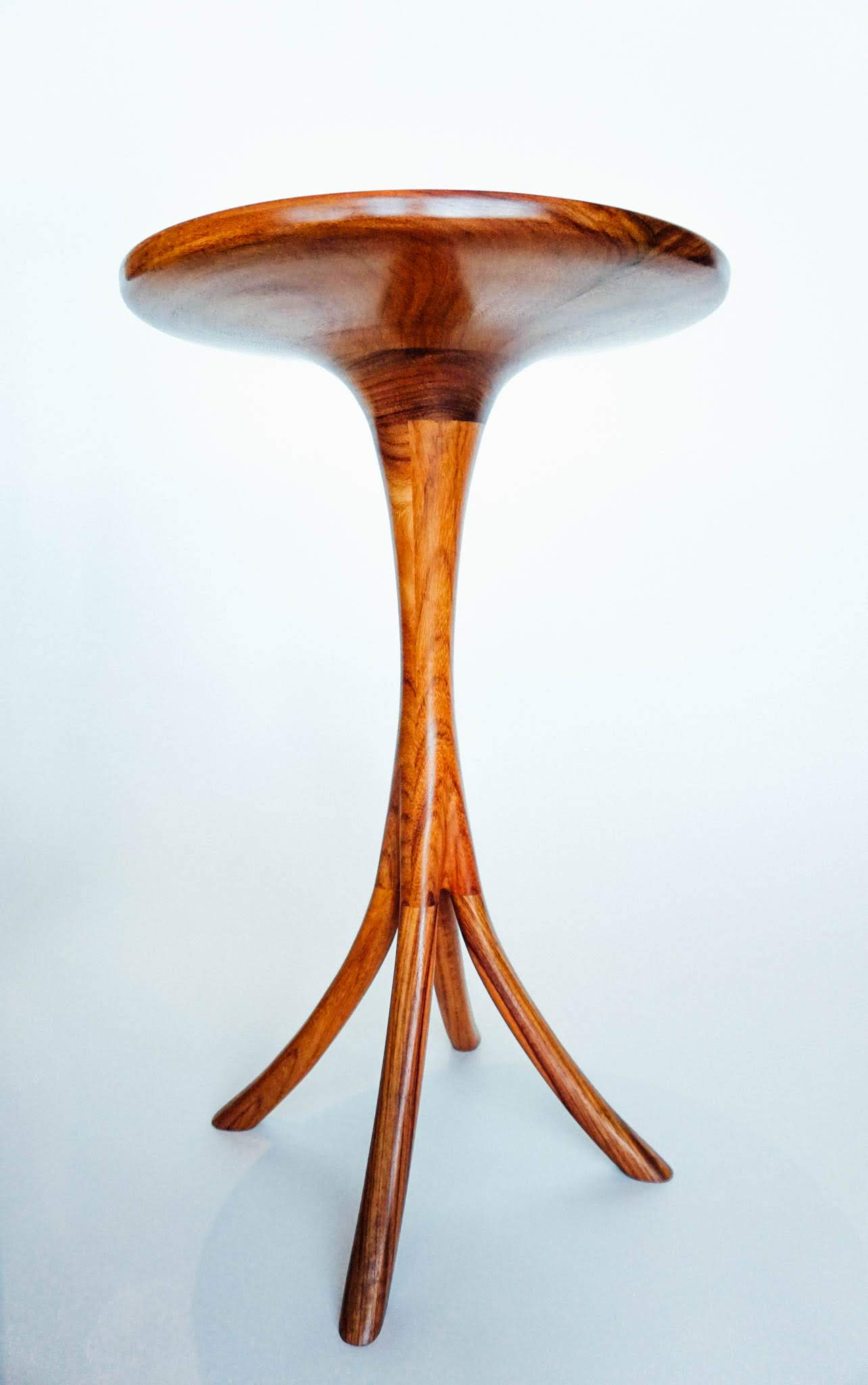The top and pedestal are turned on the lathe and joined together.  The leg transitions into the pedestal are hand carved to enrich the free flowing organic form.