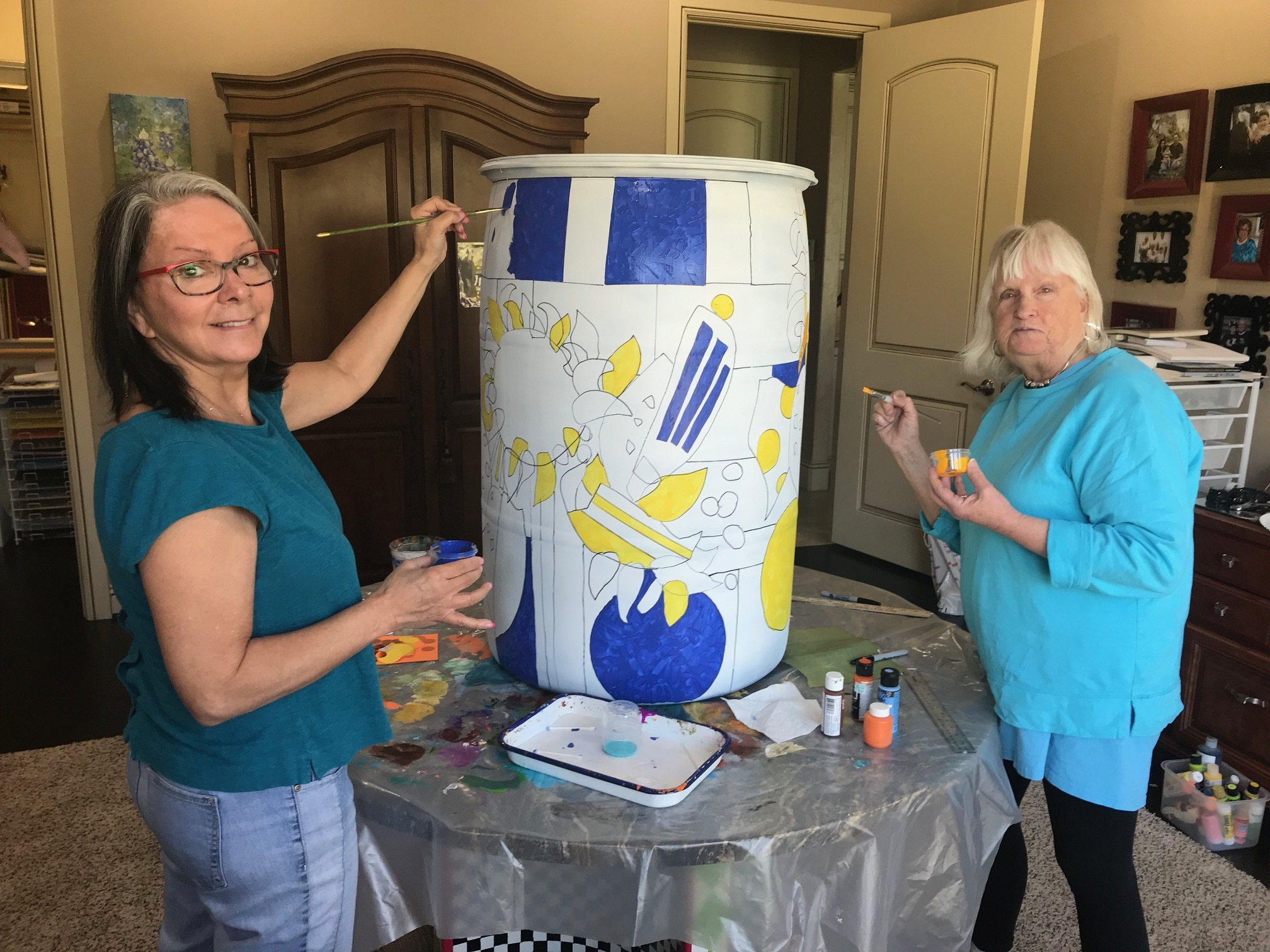 Pepper Crary (left) and Deanna Thibault paint one of the rain barrels to donate to the Earth Day 2019 Project.
