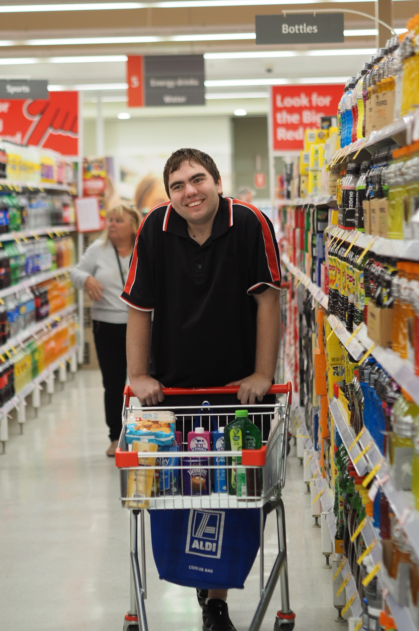 Picture of man using shopping trolley in supermarket aisle