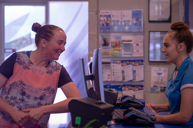 Image of woman being served by a staff member at a cash register at the local pool.