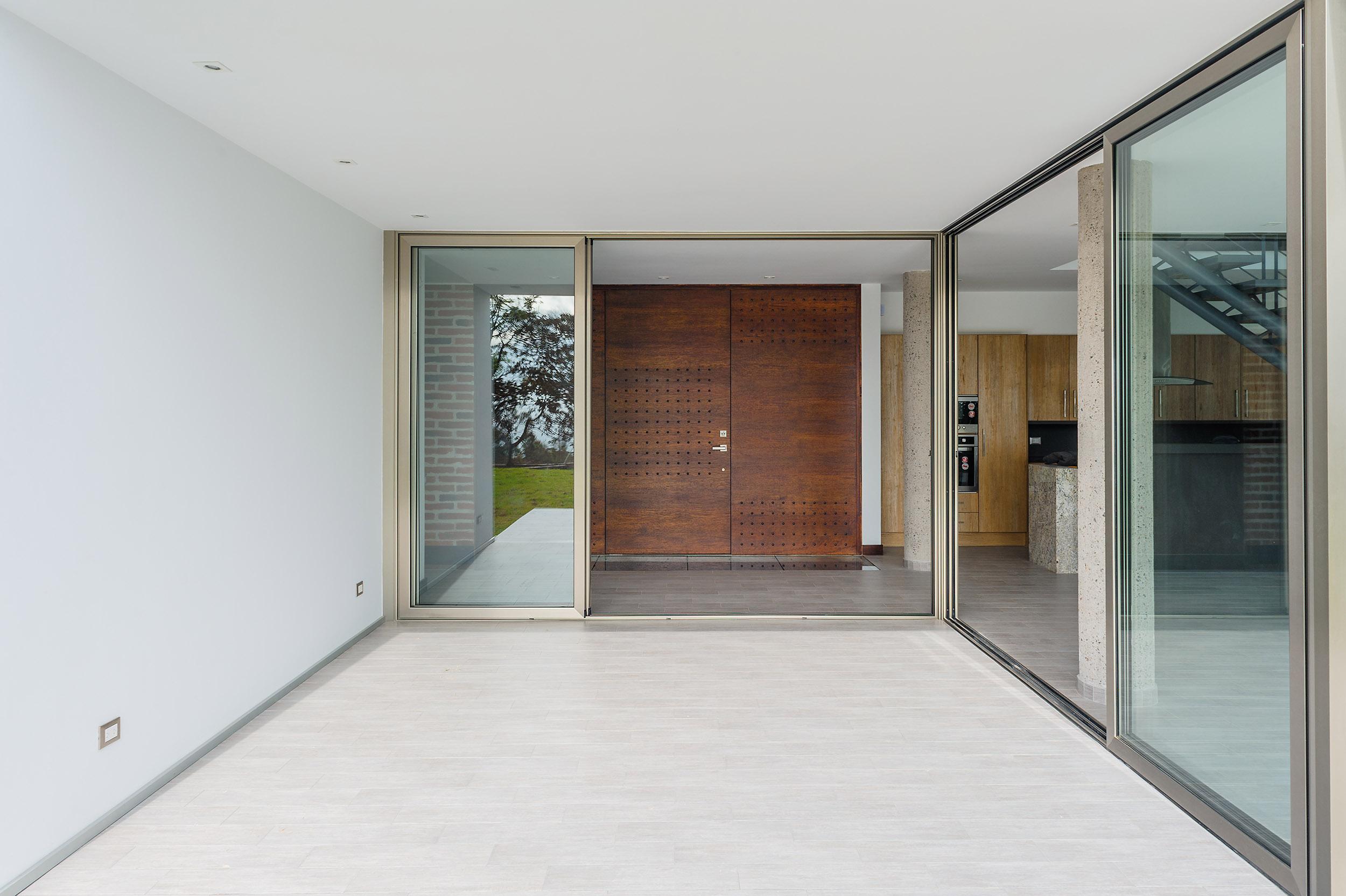 Hall de ingreso en casa, con puerta corrediza de vidrio tipo kiss