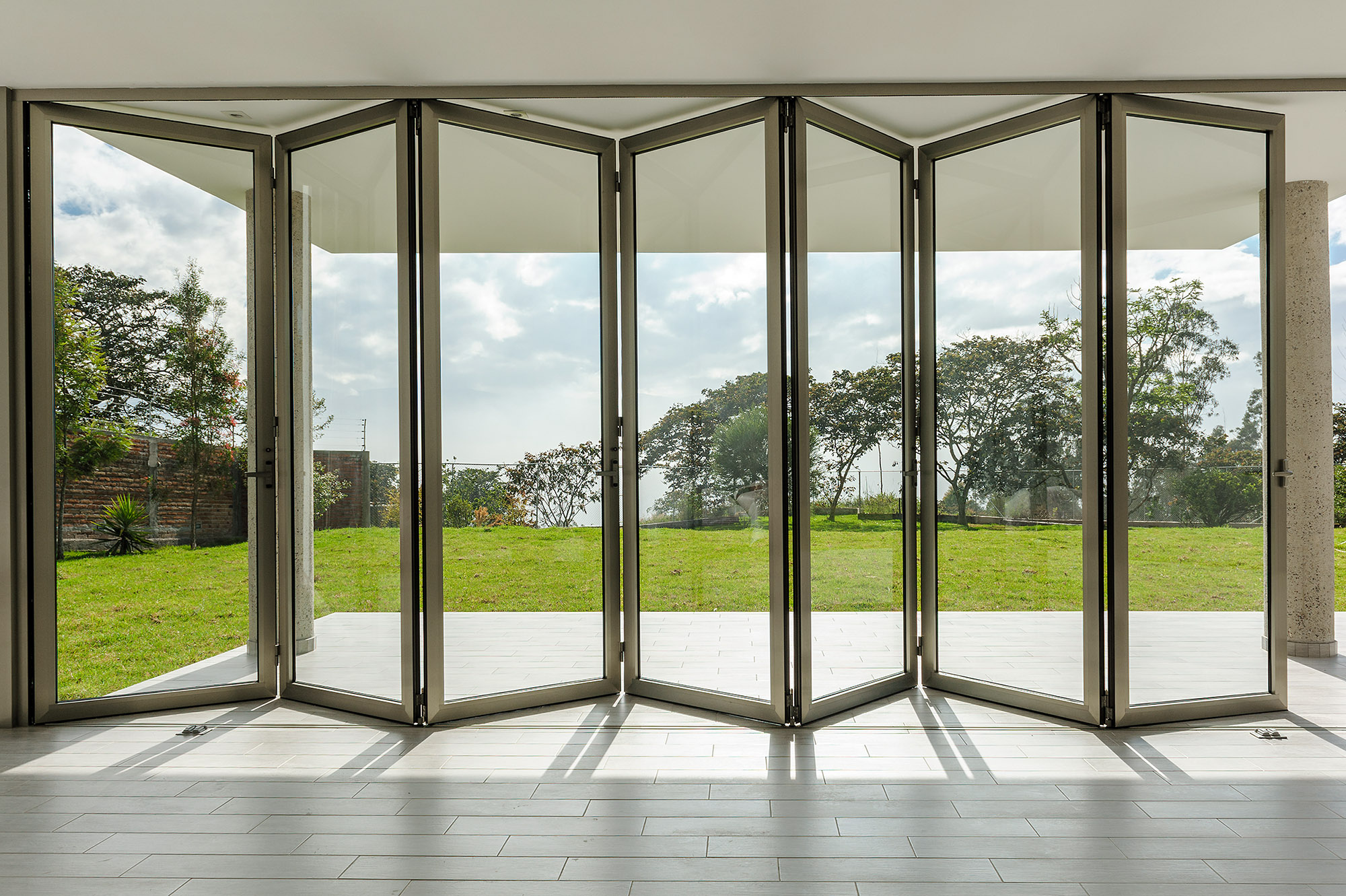Puerta plegable de vidrio en casa, con vista panorámica de paisaje exterior