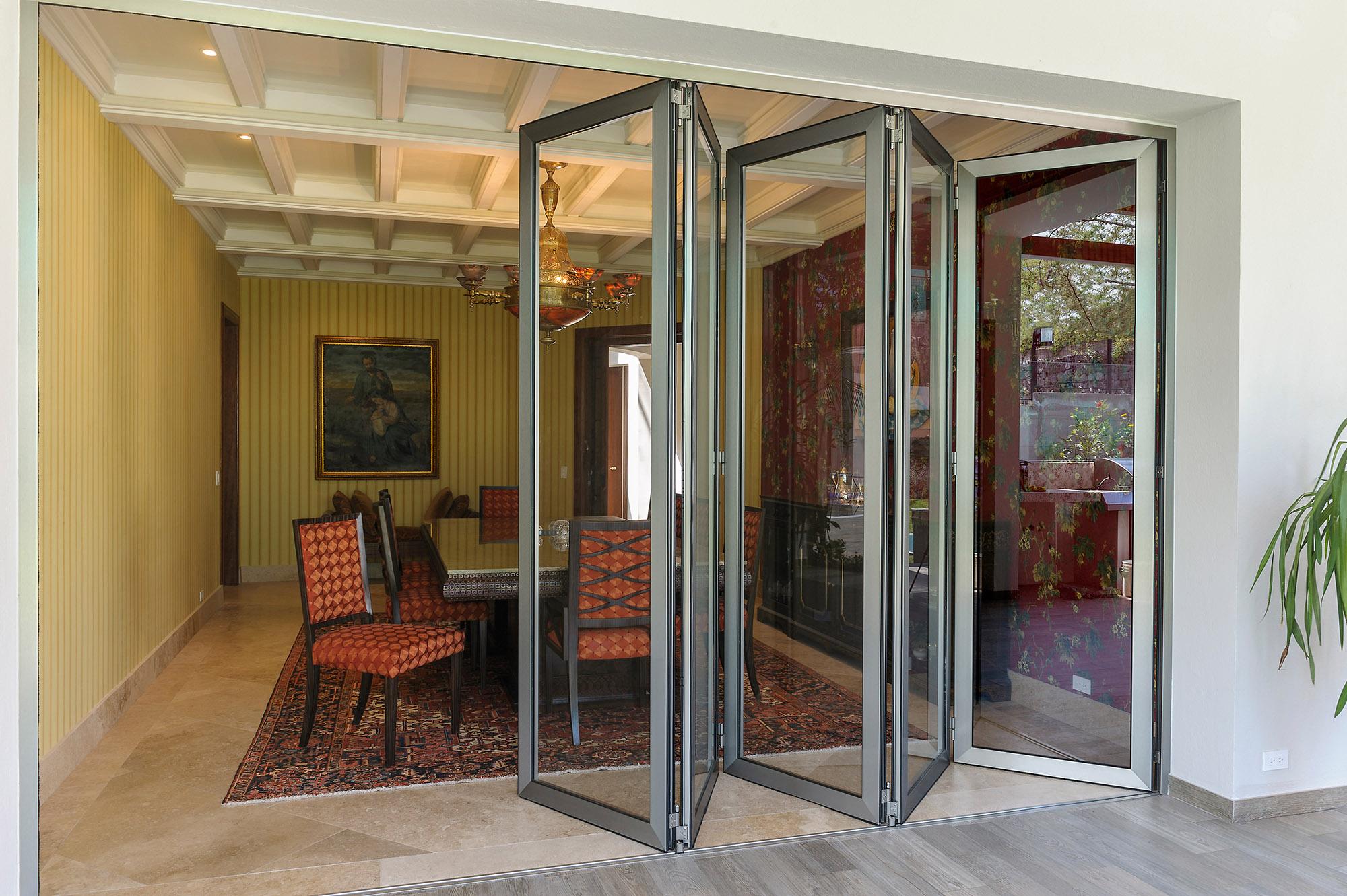 Sala de casa con puerta plegable con marcos de aluminio, abierta parcialmente