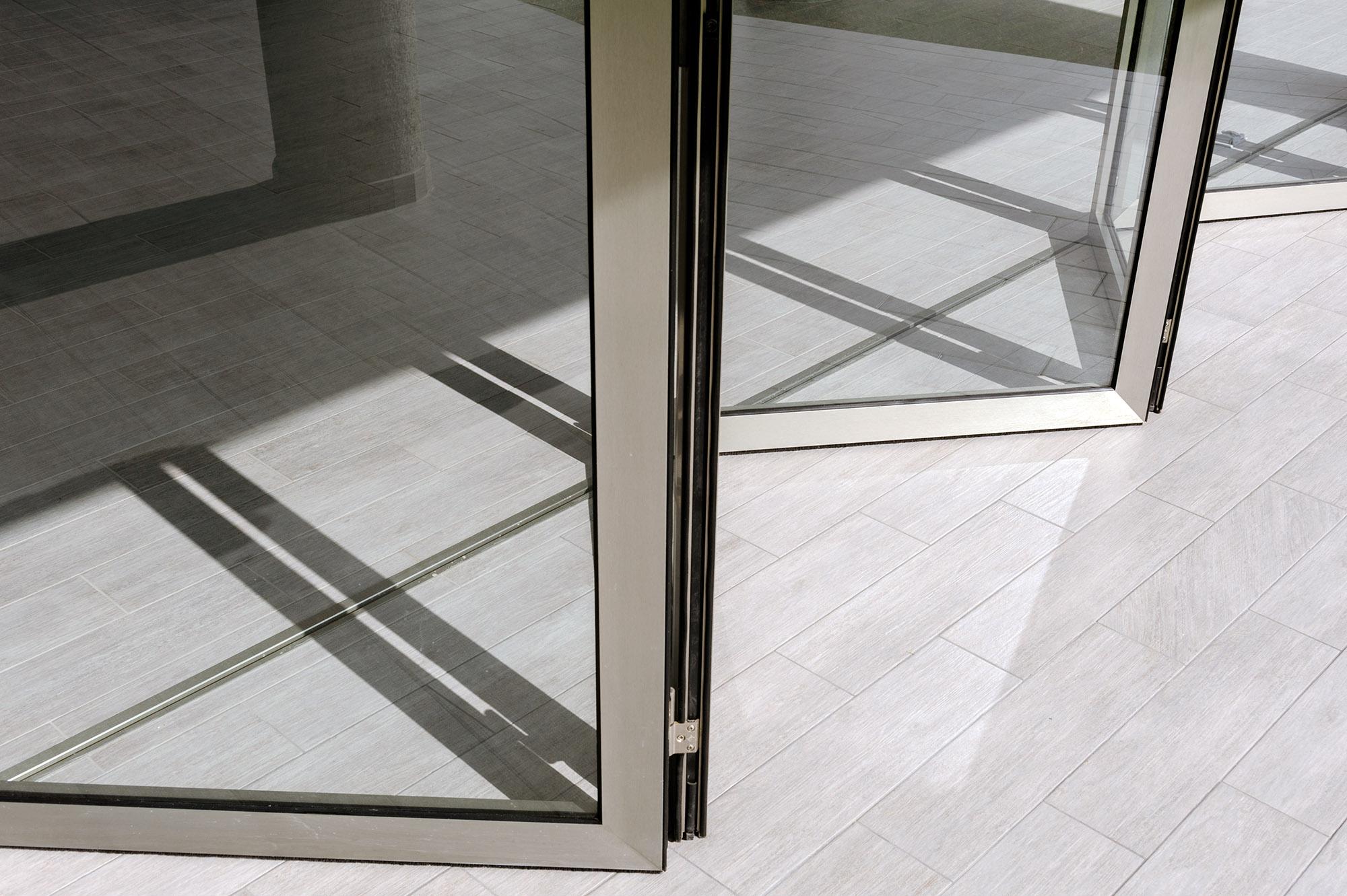 Puerta de vidrio transparente semiabierta sobre piso de cerámica y con sombras proyectadas