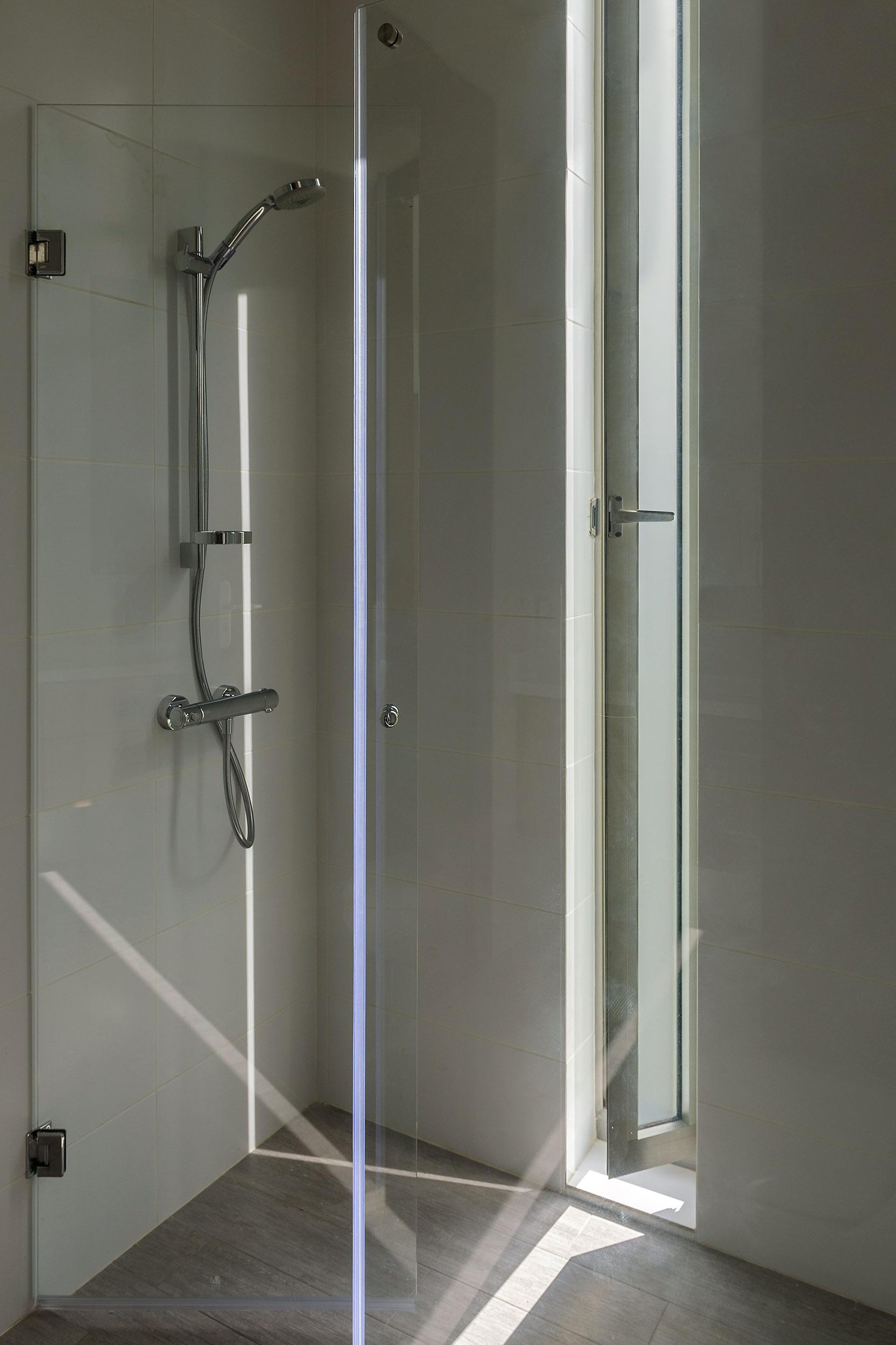 Ducha compuesta por una elegante cortina de vidrio transparente que favorece a su iluminación
