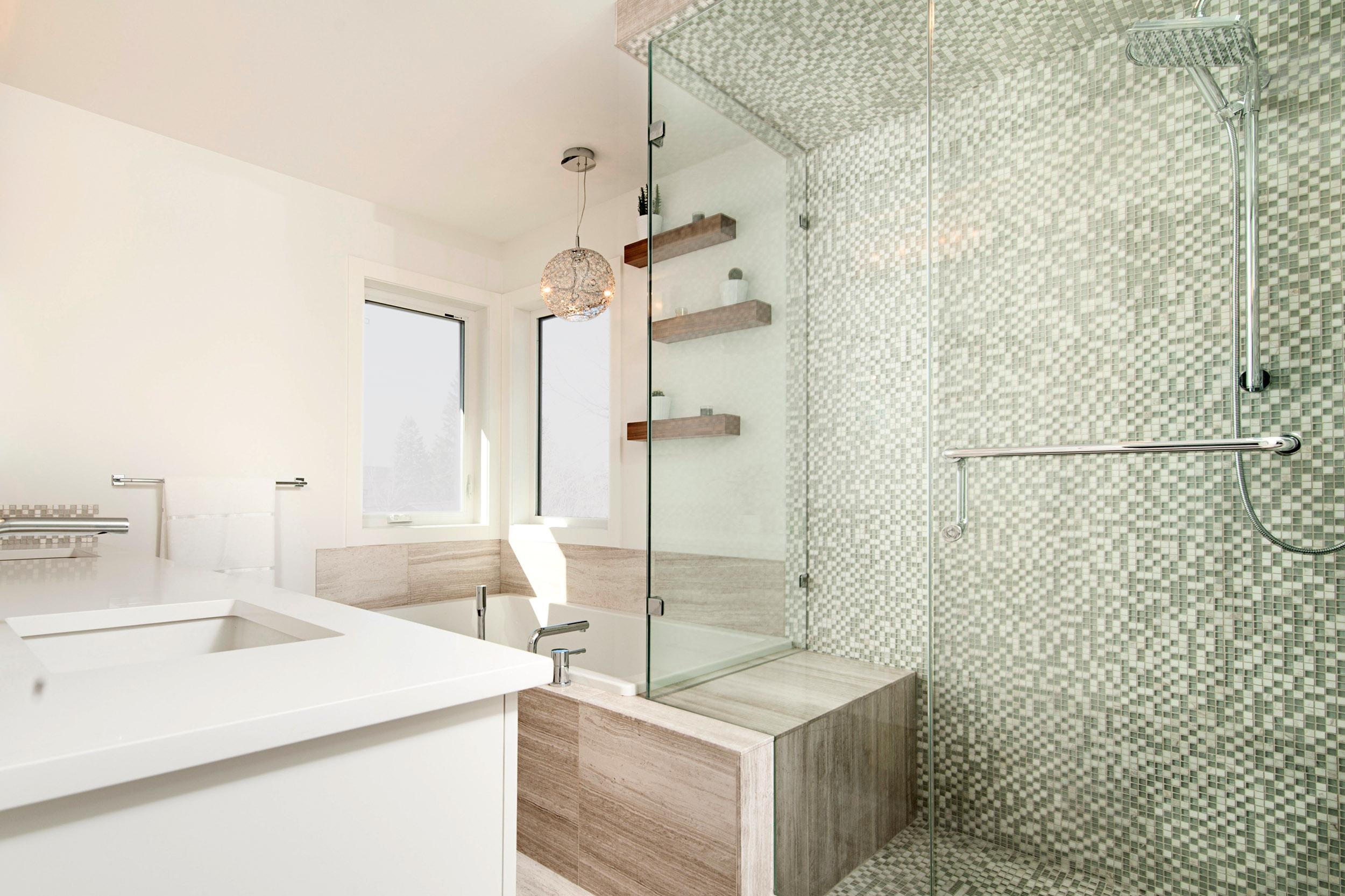 Tina con cortina de vidrio en uno de sus extremos, que complementa la decoración del baño