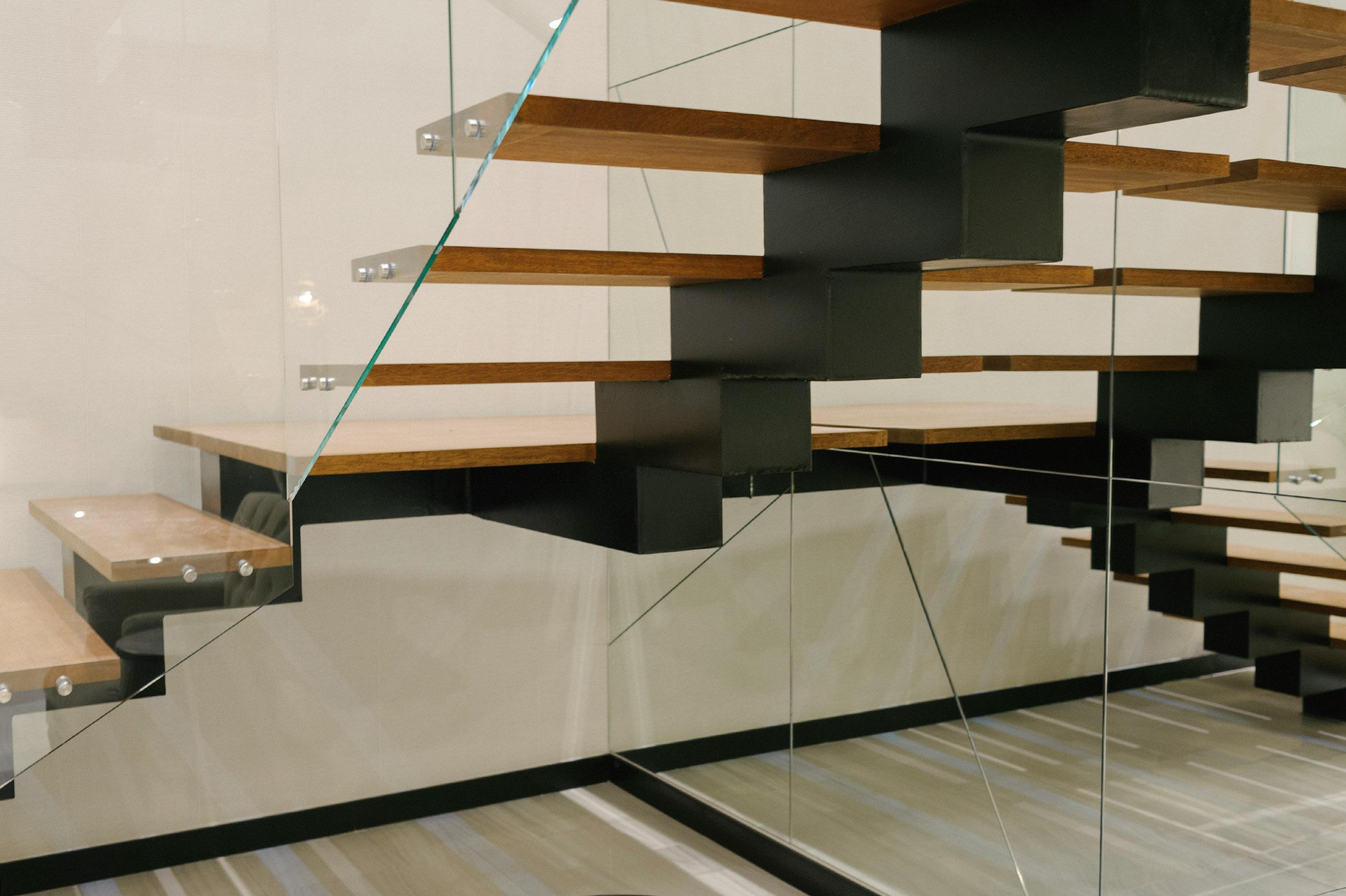 Escaleras con pasamanos de vidrio que se adapta al diseño de las gradas y le brinda transparencia