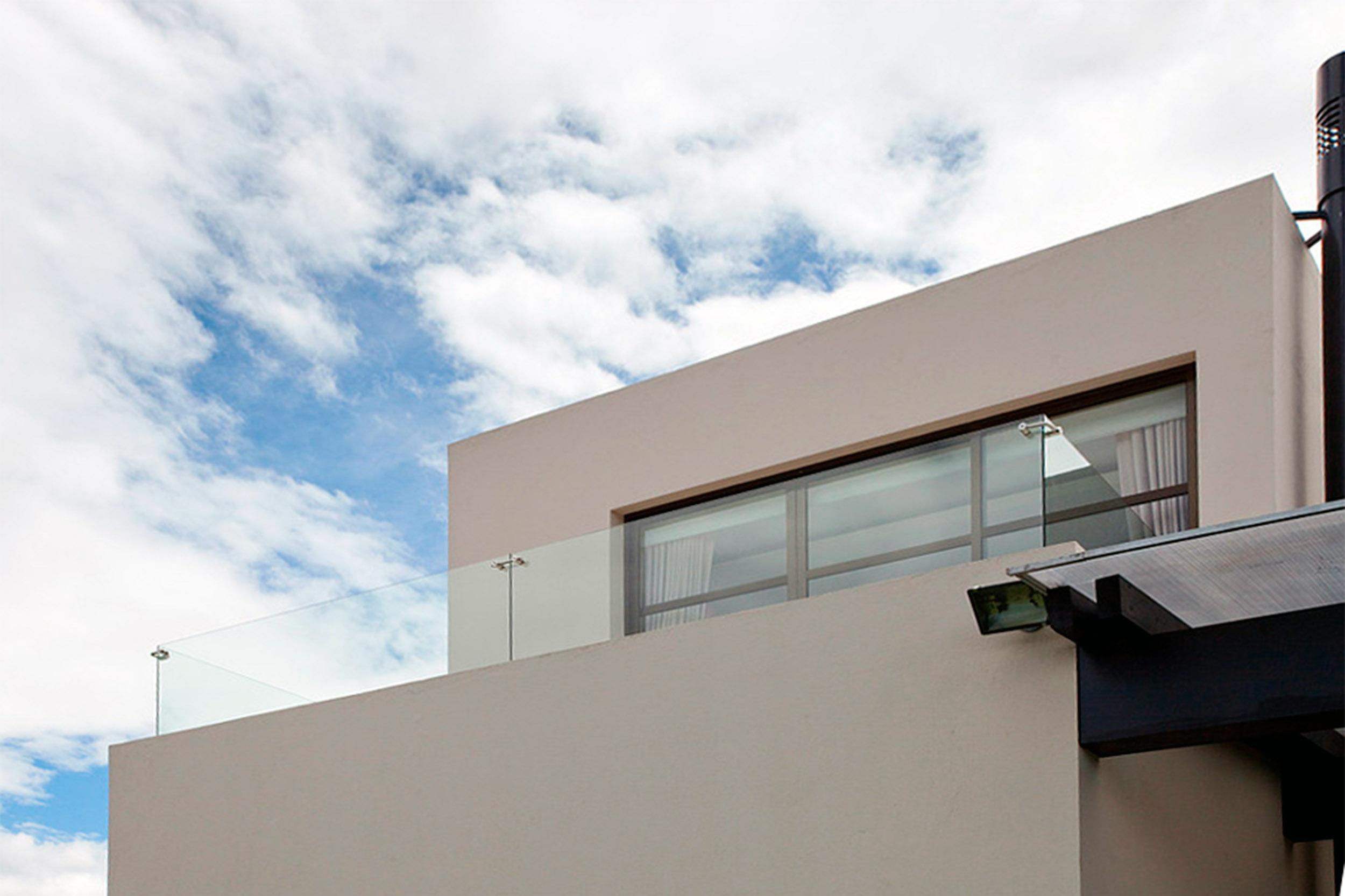 Terraza limitada por una baranda de vidrio que regula la circulación del viento