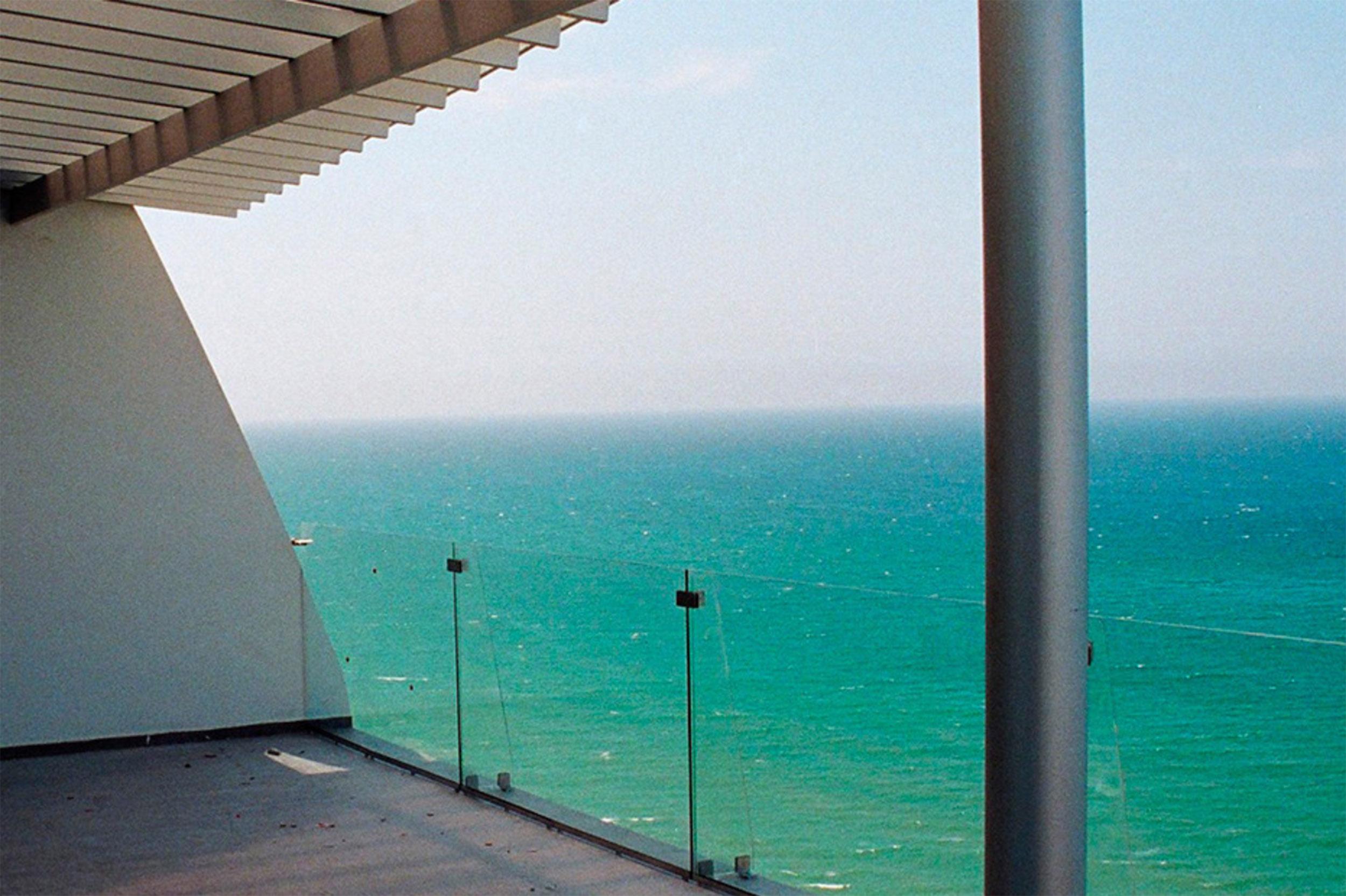 Vista del mar desde un balcón con cortavientos de vidrio