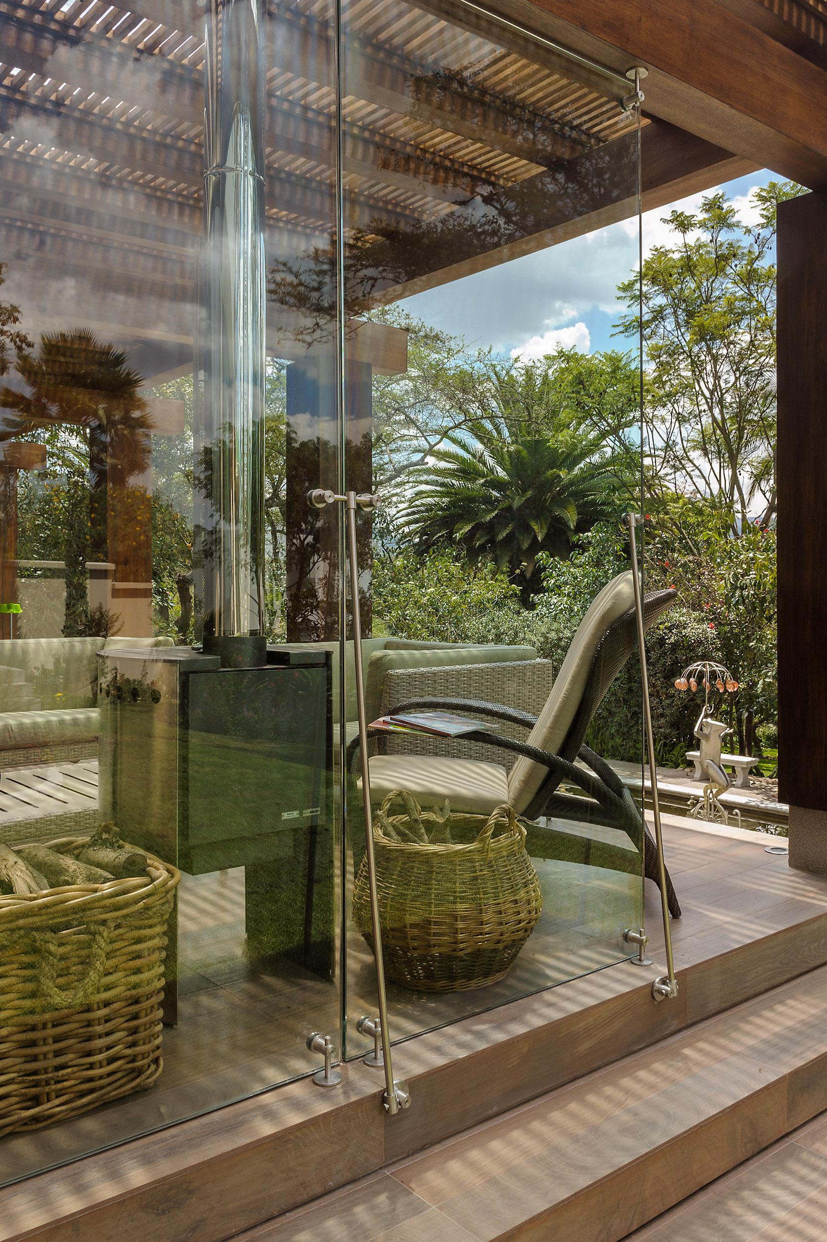 Sala exterior de vivienda con cortavientos de vidrio