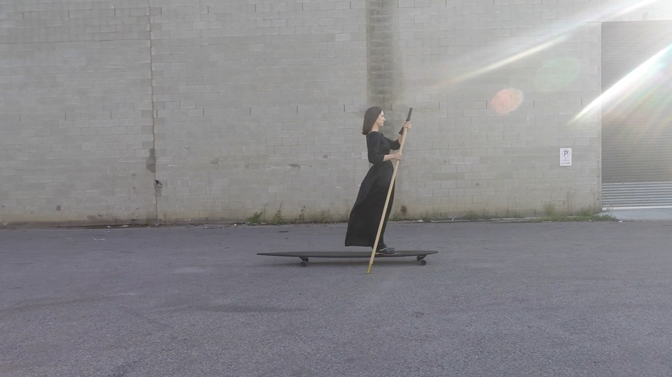 Longboard Sequence (video still), 2015  documentation of an action, single channel HD video, 16:9, colour, 2 minutes 3 seconds  In the space between wake and sleep, the figure in  Longboard Sequence  arrived fully formed, emerging out of the dark, clothed in silk, black like the night gliding along on an equally black longboard. There is a formal similarity between the Longboard character and the black swan.