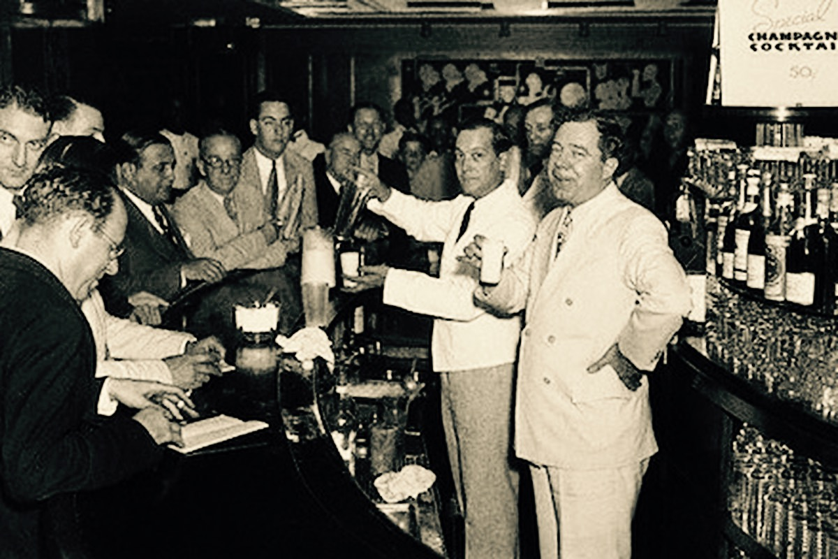 Huey P Long, Ramos Gin Fizz in hand, behind the bar of the New Yorker Hotel in July 1935
